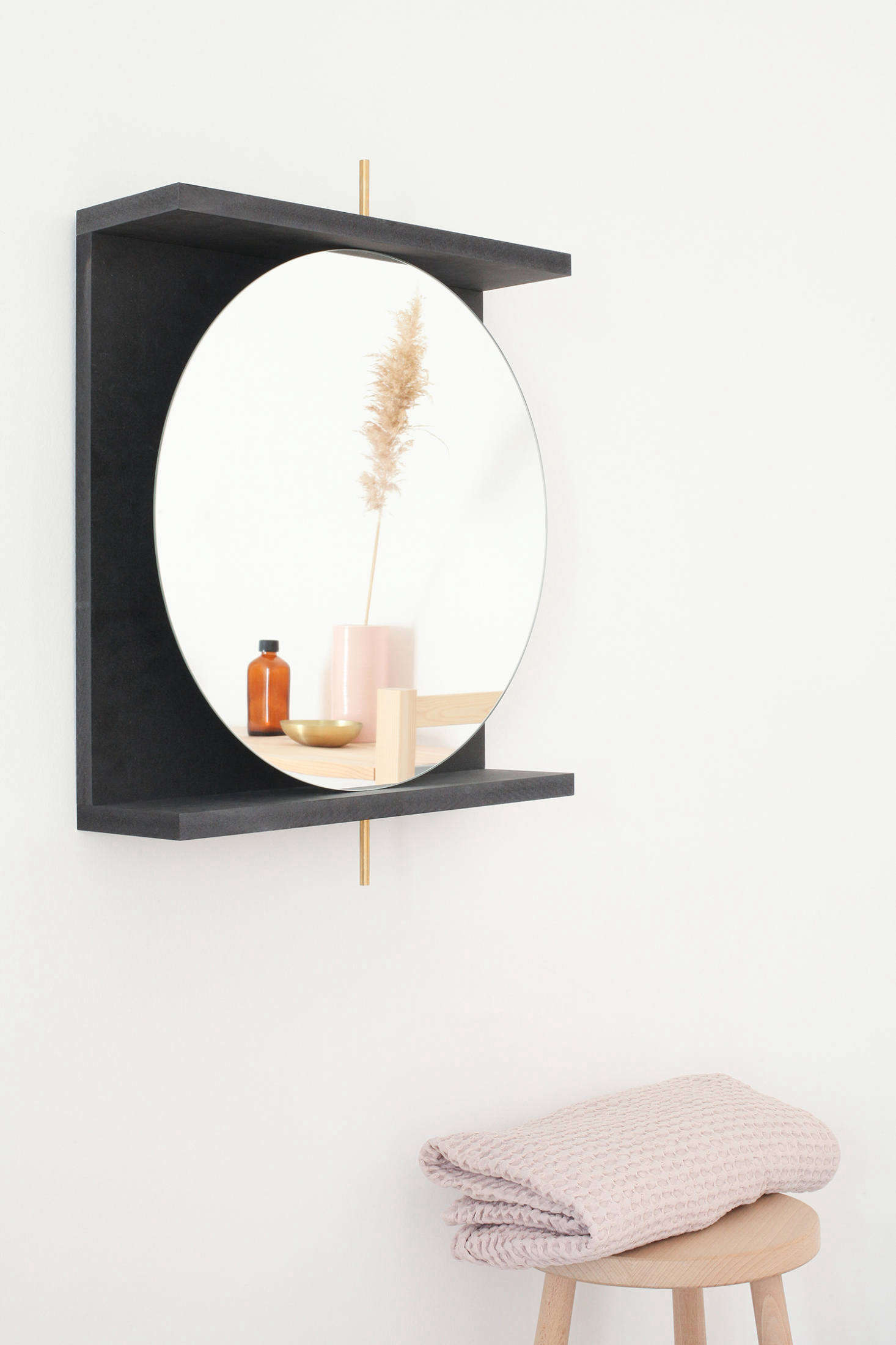 """The mirror is supported by a brass rod inserted into a water-resistant MDF frame that doubles as a shelf. The mirror pivots """"just enough,"""" the designers explain, """"that you can tuck some beauty products behind it."""""""