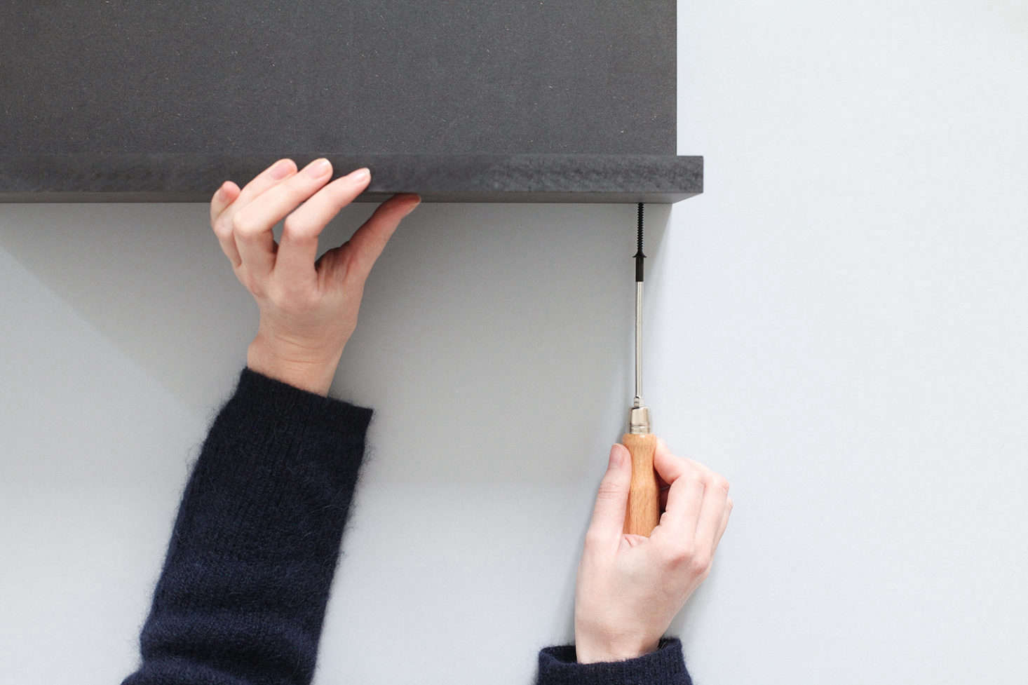 Drill 8-millimeter-wide holes into the top and bottom panels, 3.5 centimeters from the edge (one hole in the center and one at each end). Widen the holes as needed with your drill and screw the bottom panel to the back. N.B.: The designers recommend using black screws.