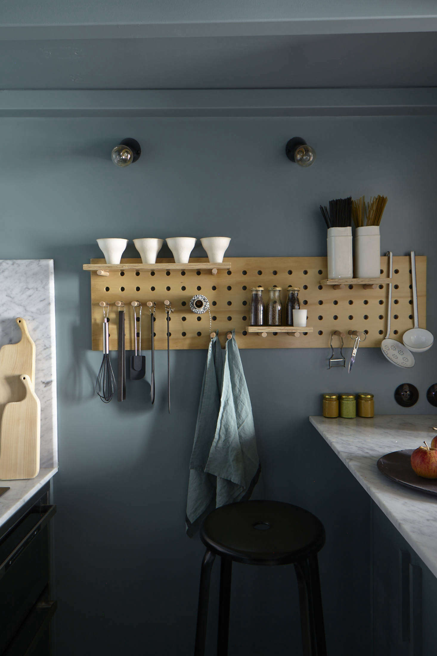 A pegboard makes use of the small space and keeps tools, towels, and twine within easy reach. The flush-mount light bulbs are from Zangra.