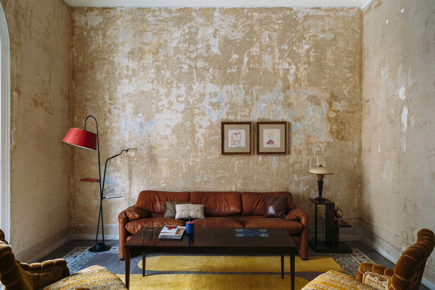 A 1970s leather sofa looks surprisingly at home in the stripped-bare living room.