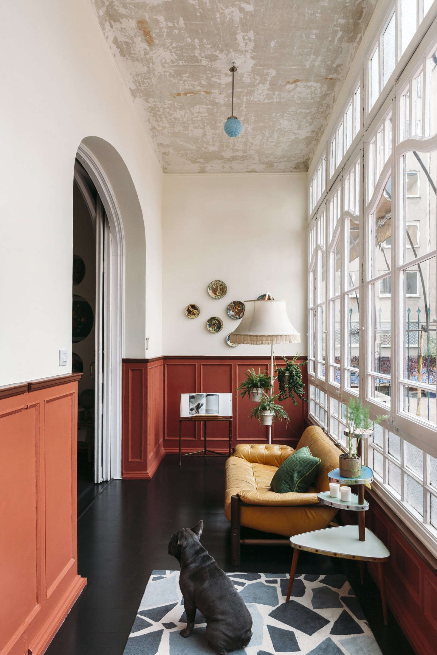 An arched entry leads to a long, narrow lounge with its original divided glass wall and a refinished ebonized floor. The designers scraped away the ceiling paint and left it as is, detailed with a small blue milk glass pendant.