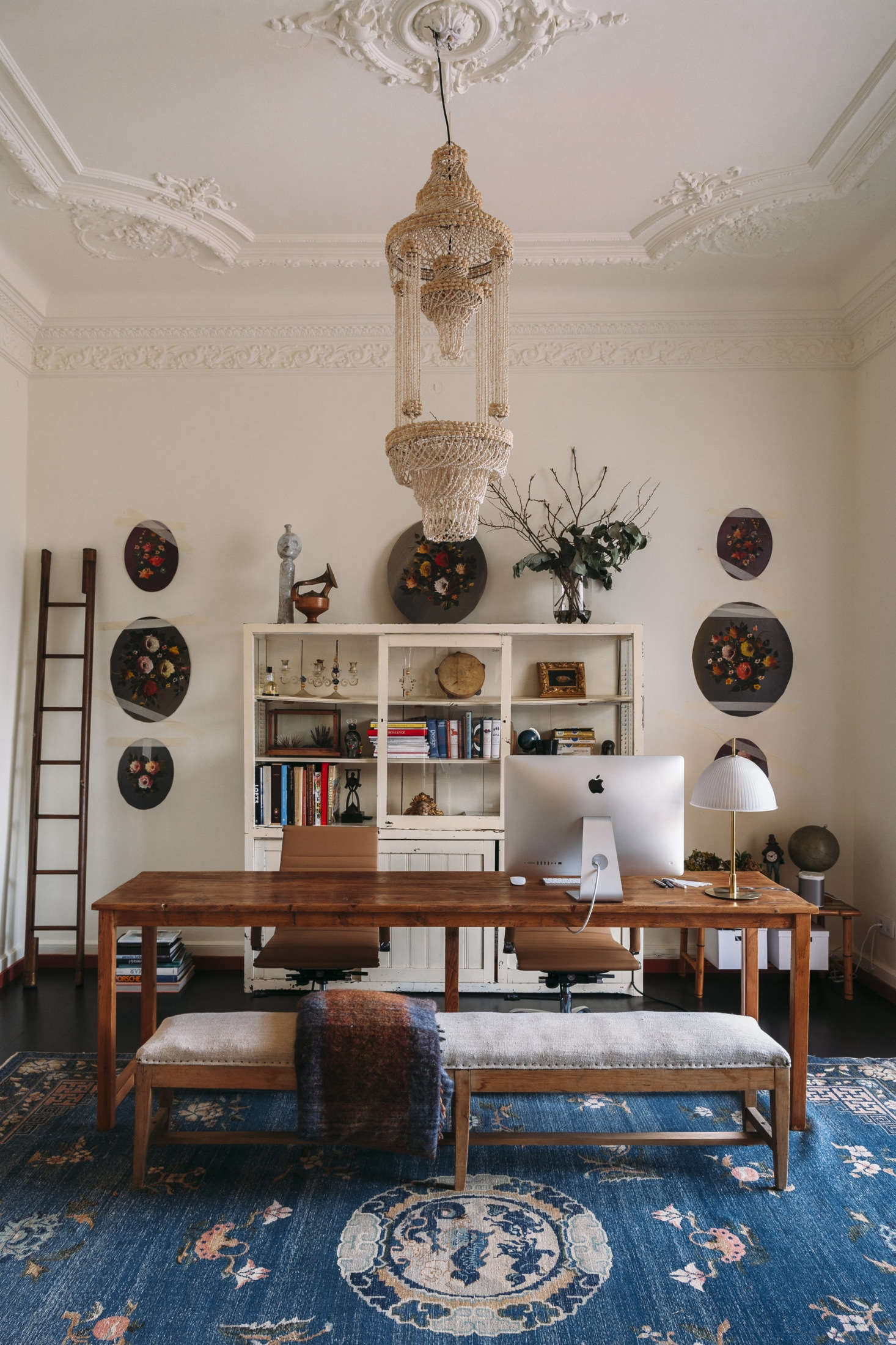 Off the entry, a work table stands on a Chinese art deco rug under a beaded chandelier.