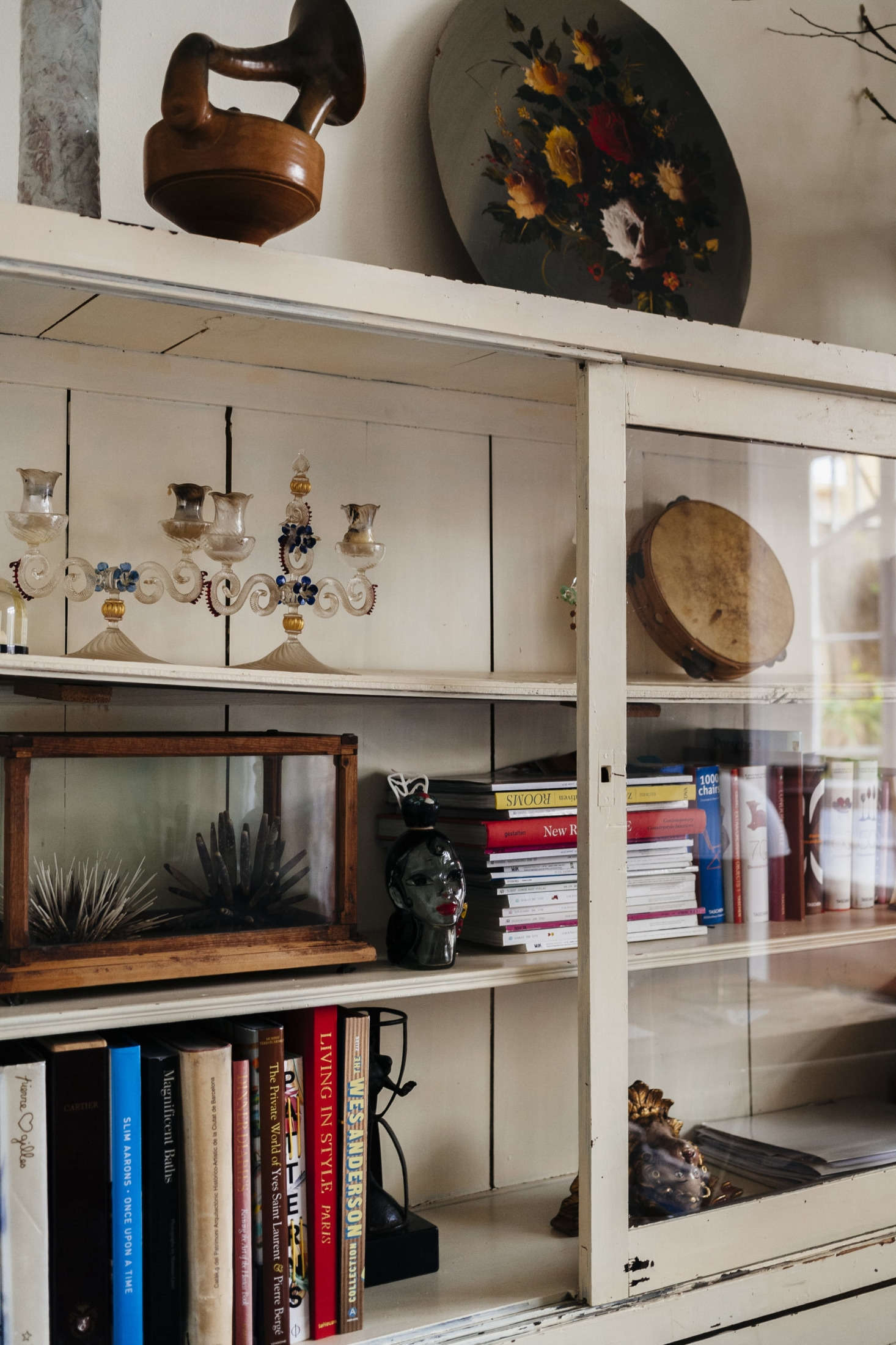 Design books and magazines are surrounded by some of the duo's latest finds, including a pair of Venetian glass candelabra and a Wardian-style terrarium case.