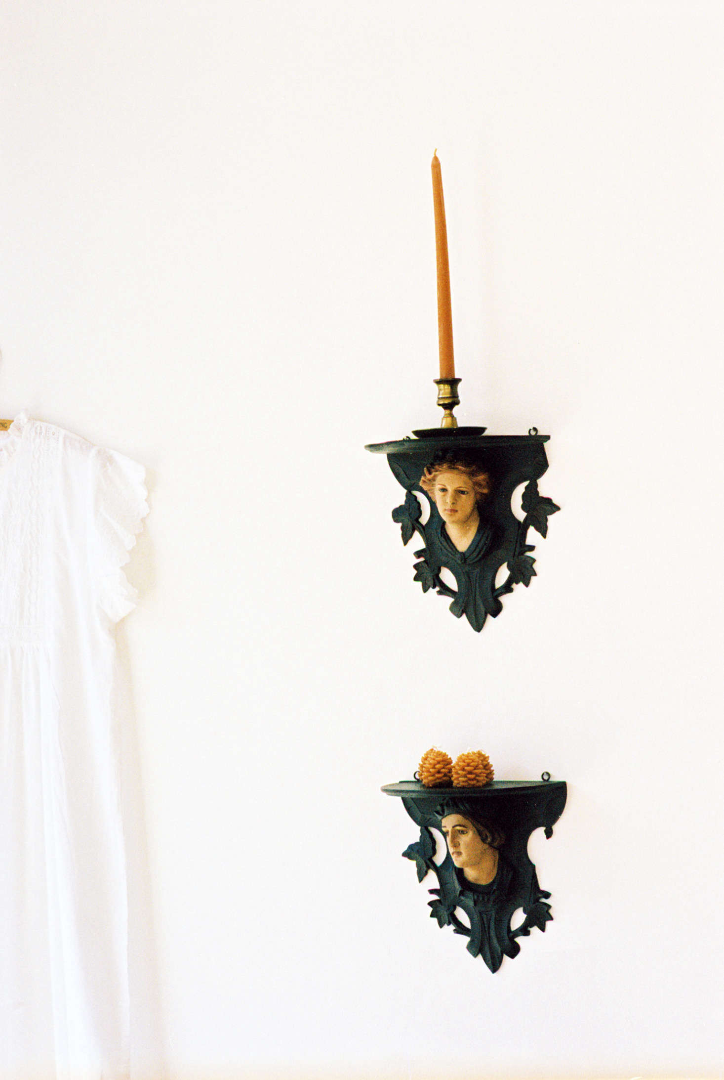 Shelves with a slightly gothic air hold Wee Pine Cone Candles ($24 for a box of four).