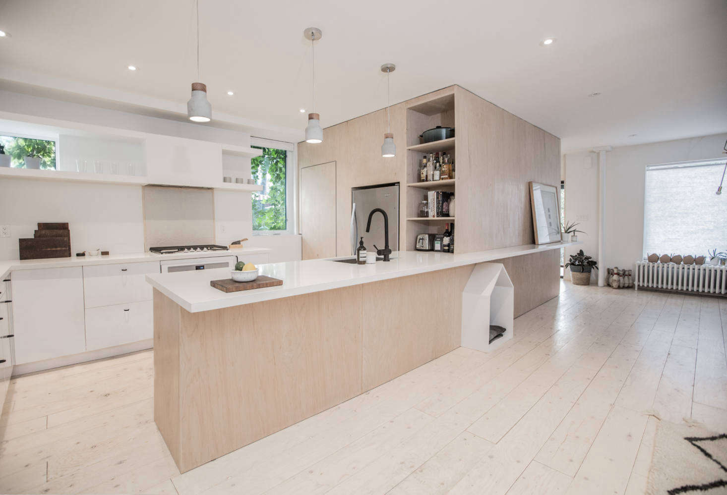 The kitchen is fitted with simple white Ikea cabinets paired with custom overhead open shelving of painted wood. The counters are white CaesarStone (read about it in Remodeling 101: 7 Things to Know about Engineered Quartz Countertops).