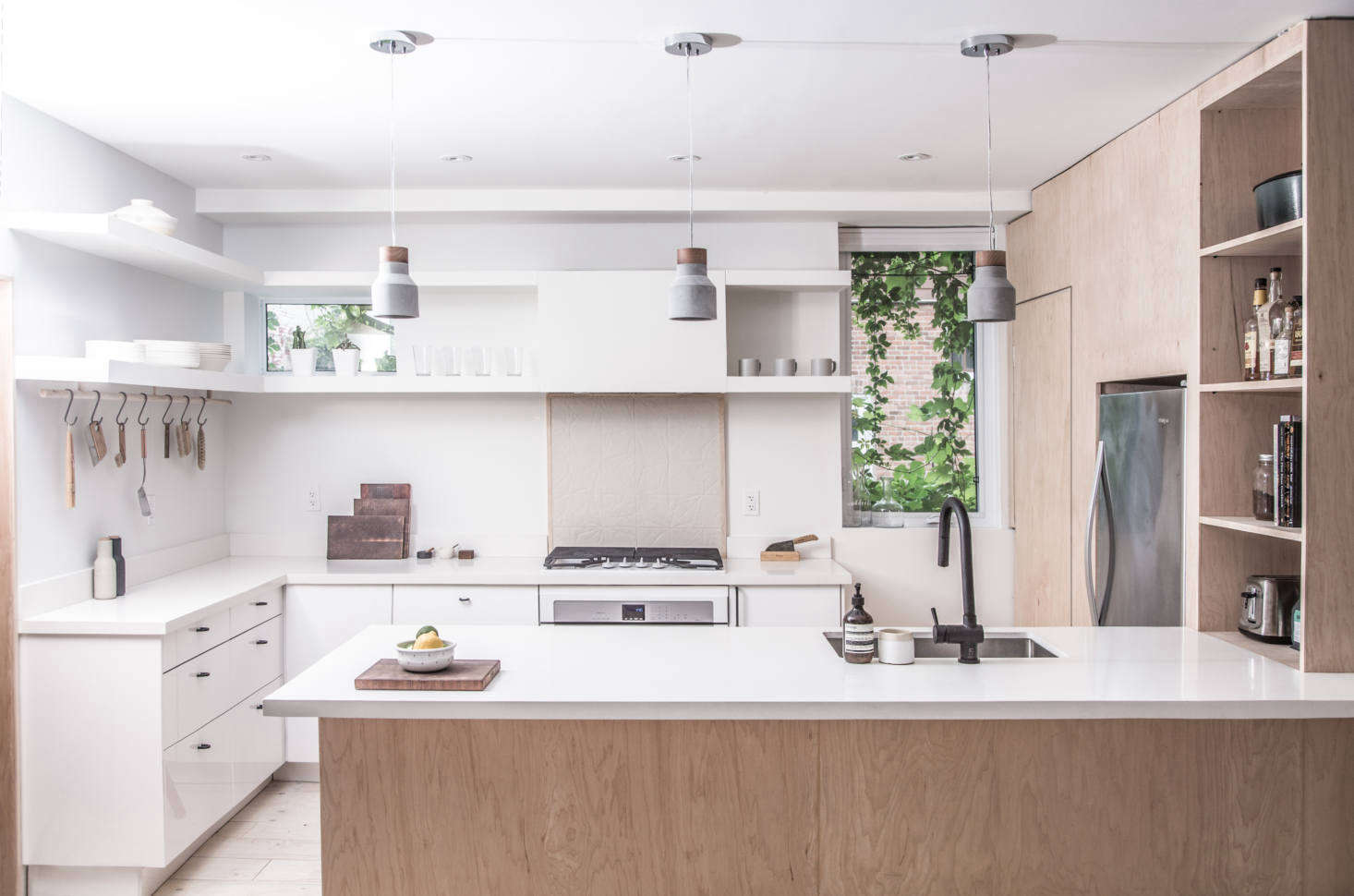 The refrigerator is fitted into the plywood volume but left undisguised. The range has a tiled backsplash and the two-tiered overhead shelves conceal the exhaust fan.