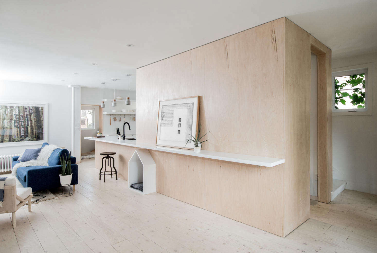 The kitchen is integrated into a floor-to-ceiling birch plywood structure that also contains a foyer, closet, and stairs.The wide-plank floor is lightened plywood sealed with a matte polyurethane.
