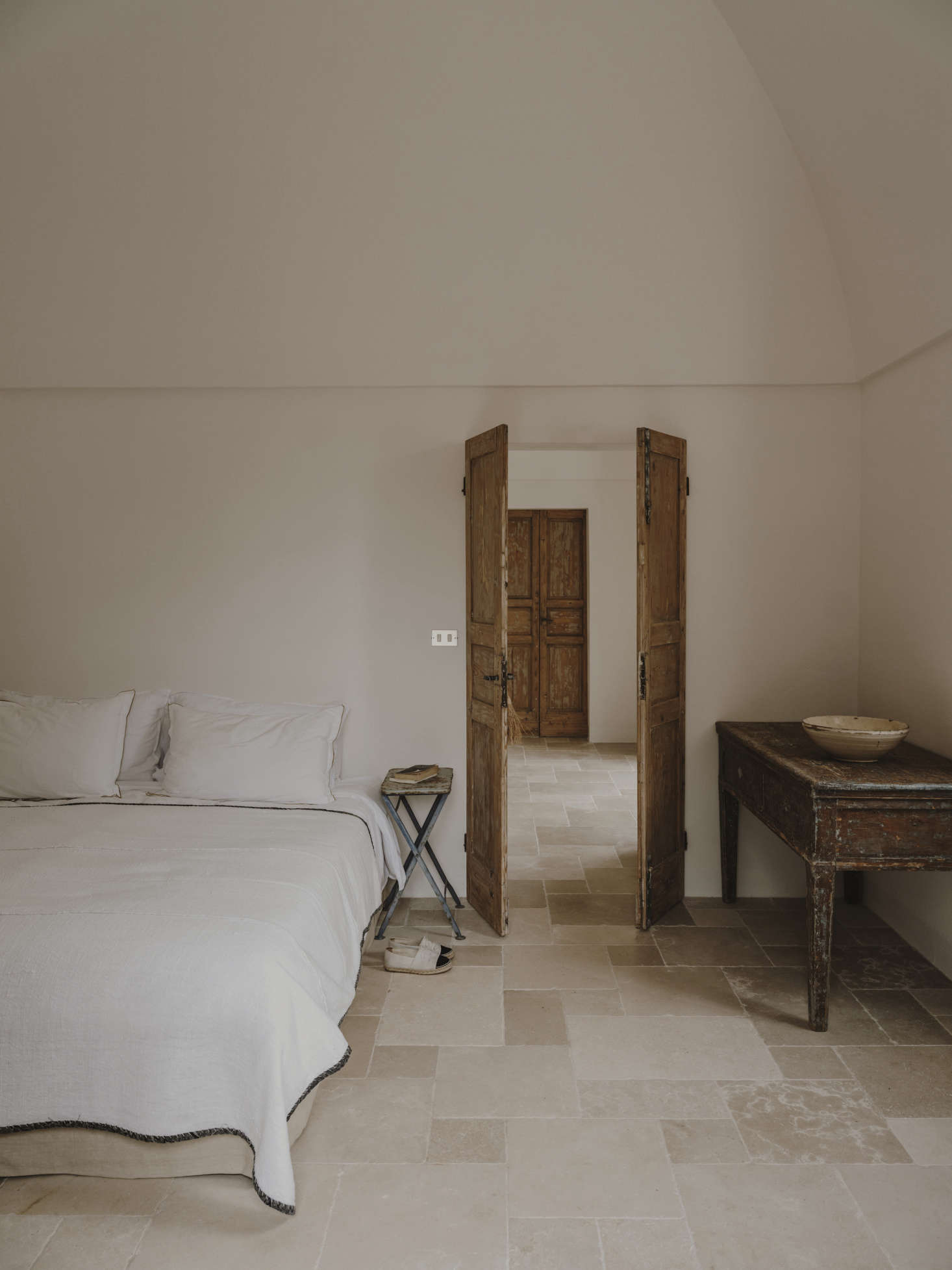 One of the three guest rooms, with simple, airy fittings and a black-trimmed coverlet.