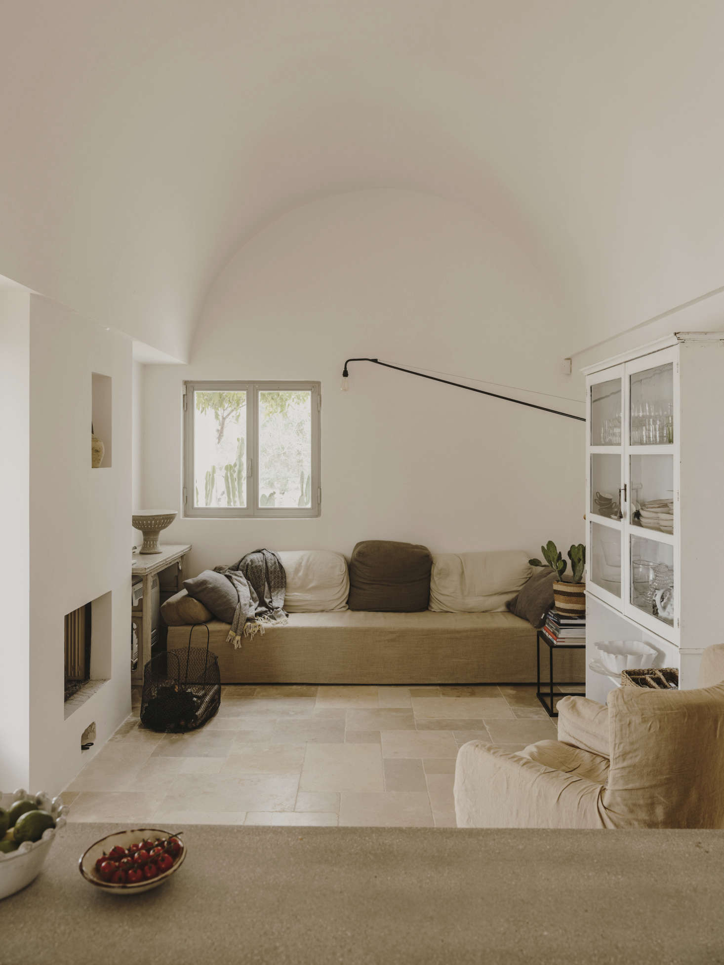 A casual living area features a low-slung, ad-hoc couch, a glass-fronted cabinet, and a long-armed black wall light. For similar lights, see10 Easy Pieces: Simple Swing-Arm Wall Lights.