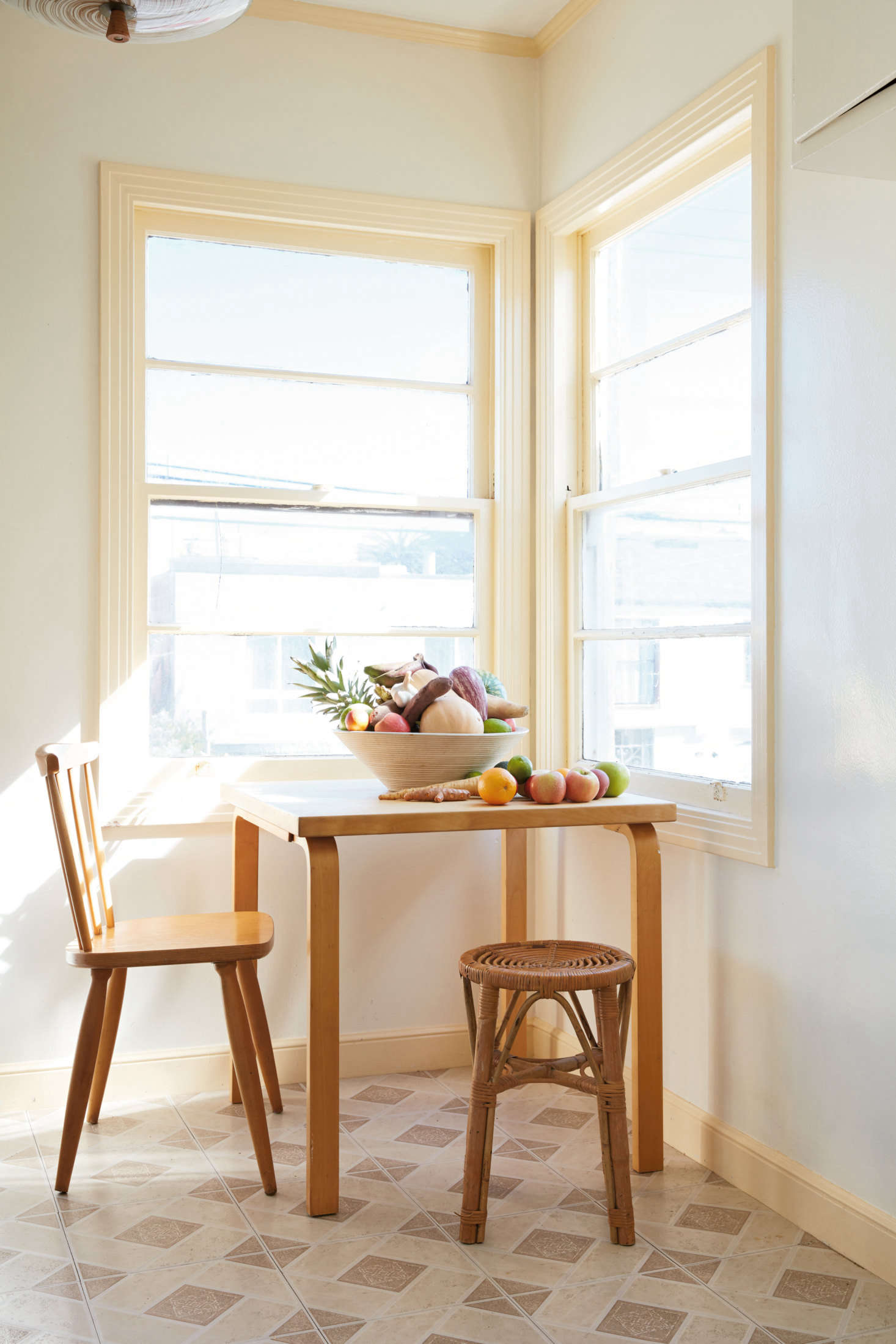 """A breakfast nook in the couple's Great Highway apartment exemplifies what they call """"the mix"""": furniture and fittings that """"represent a sort of map of our lives and our tastes,"""" all tied together by a neutral palette and natural materials. Here, an Alvar Aalto table mixes with a rattan stool, a flea market find."""