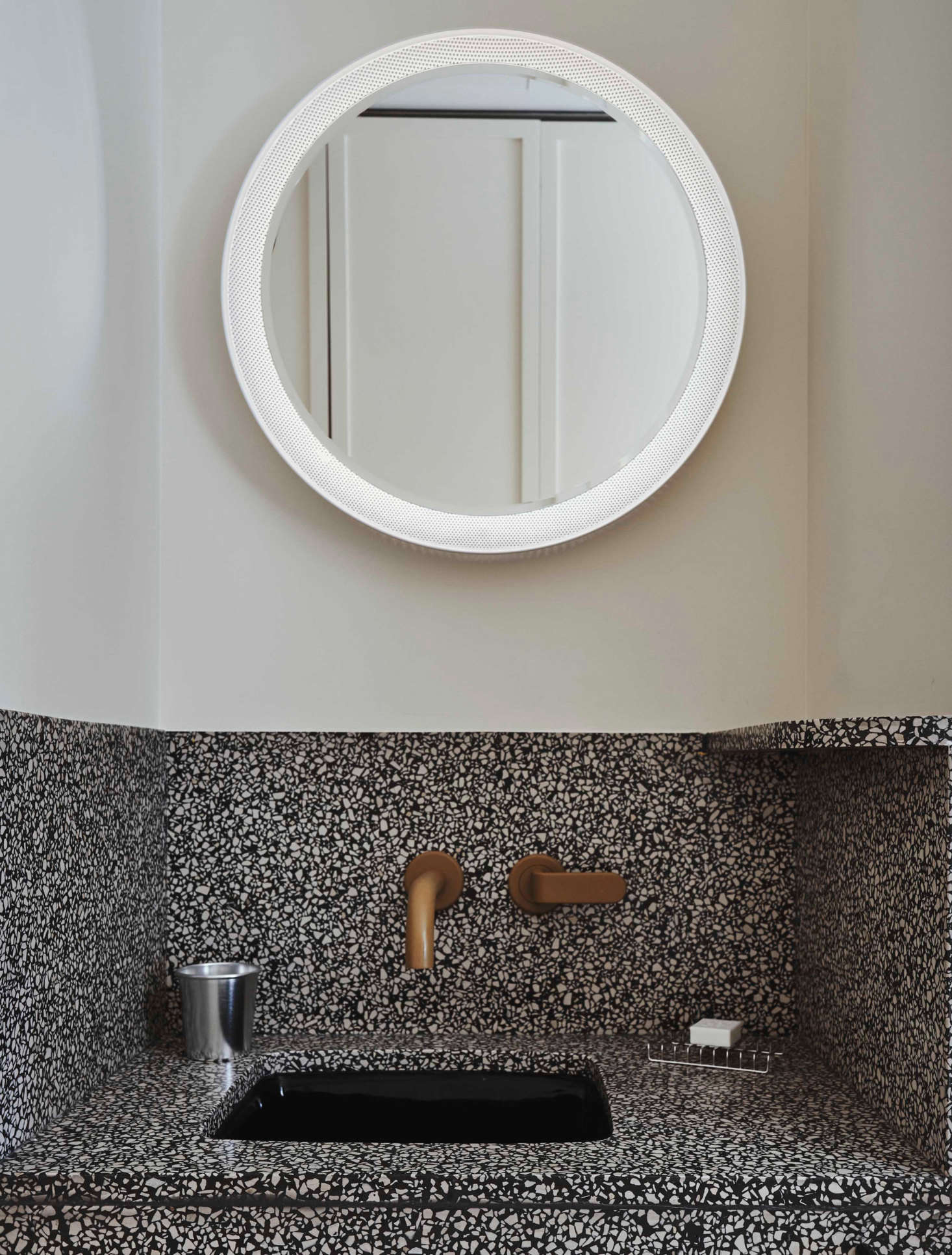 A terrazzo sink is tucked in a corner of the bedroom.