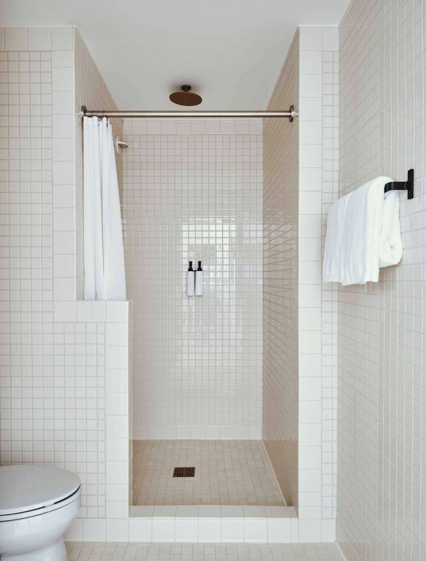 A simple white tiled guest bathroom.