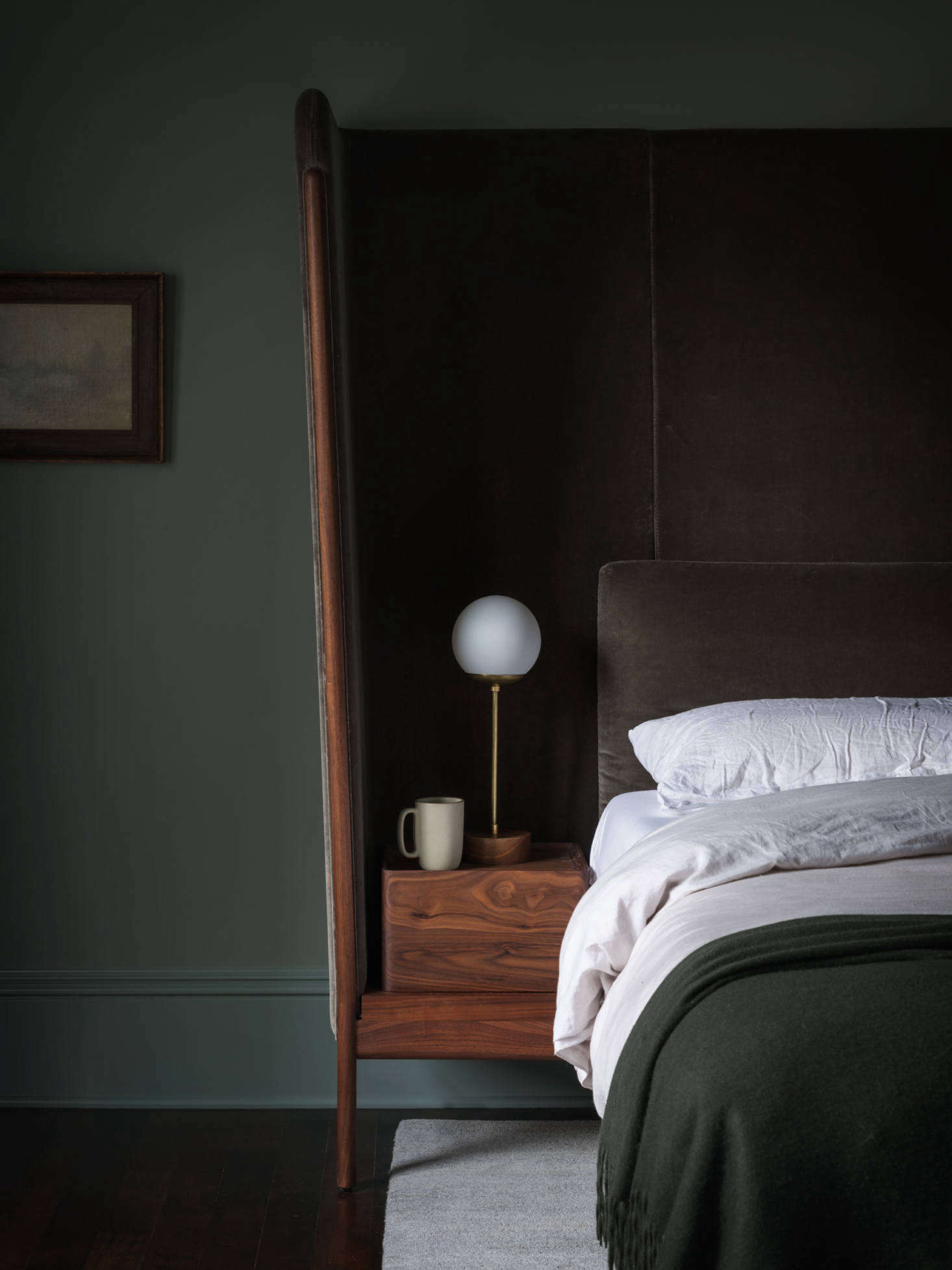"Neri & Hu also designed the bed with built-in nightstands. ""It's upholstered in cotton velvet and capped with walnut,"" she shares. The bedstand lamp is by LA-based Nino Shea."