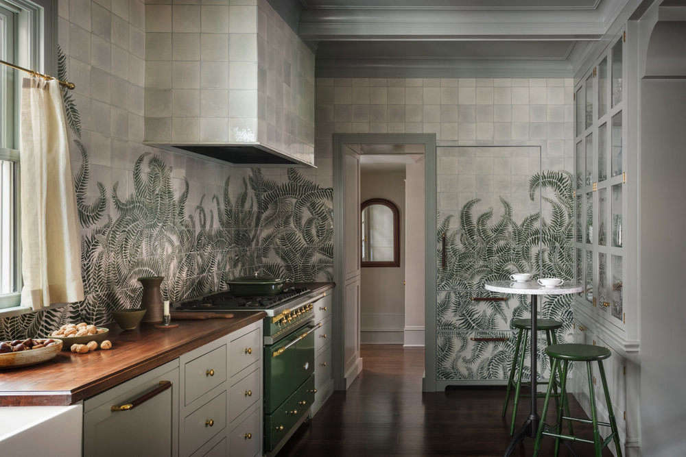 "The mural extends to every wall in the kitchen—and even covers the built-in refrigerator ""to achieve a seamless fern-scape throughout the room,"" she says. ""Our clients were onboard with our aesthetic direction for the house, which was 'an ode to the Pacific Northwest.' This led us toward furniture and decorative lighting that are markedly modern with lush mossy tones and plenty of Western walnut."""