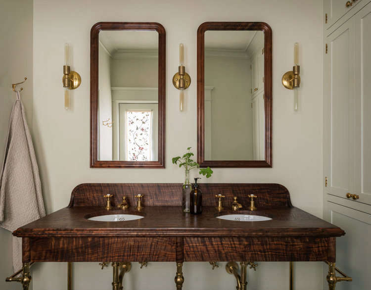 "In the bathroom, a custom-designed vanity ""made from some beautiful figured Western walnut"" steals the show. The sconces are by Michele Varian."