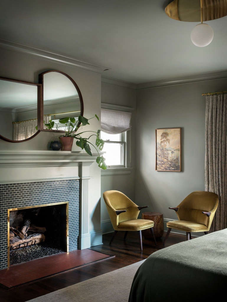 Two mirrors by Marrow hang over the fireplace in the master bedroom. The fireplace surround features handmade ceramic tiles by Pratt and Larson. The walls are painted Benjamin Moore Heather Gray.