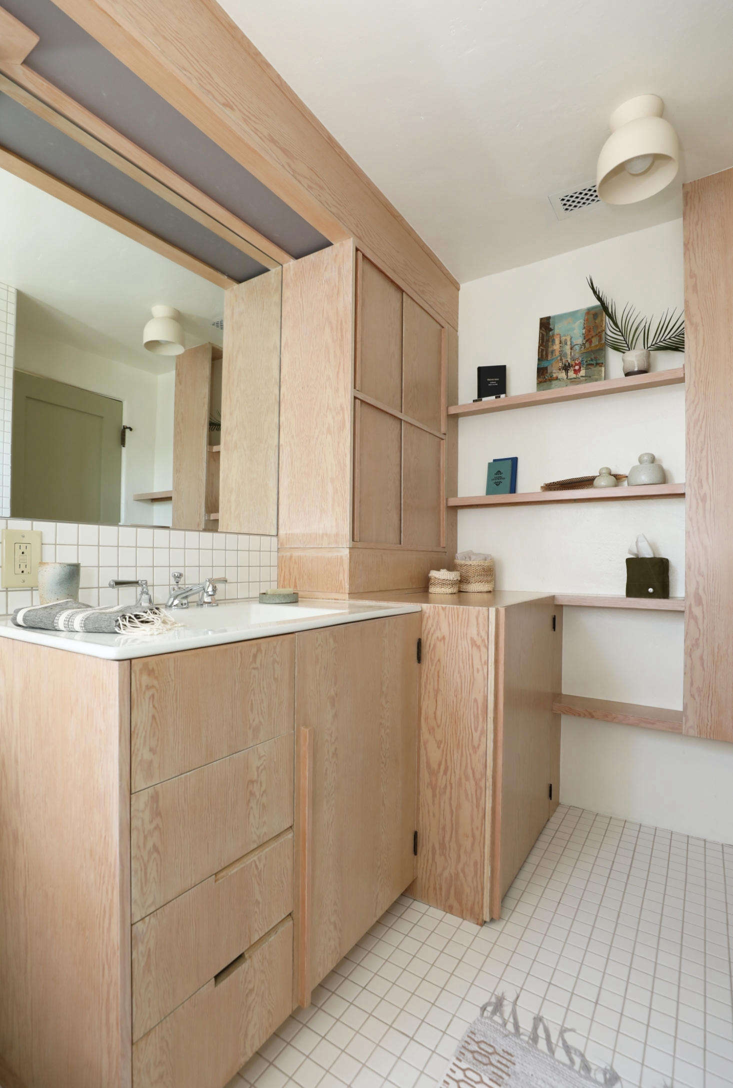 Luis Guerra Woodworking made all the cabinets in the kitchen and bath. A dual washer/dryer unit is concealed behind the deep cabinet. The Terra Surface Ceiling Light is by Cedar and Moss.