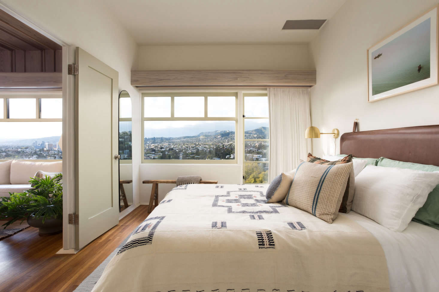 The small bedroom features linen bedding by Five/Six Textiles, a custom leather-wrapped headboard, and views of Los Feliz. Photograph by Virtually Here Studios.
