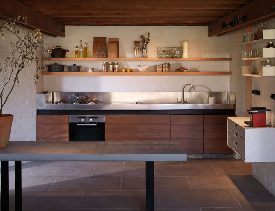 """""""The bespoke stainless steel counter was designed as part of the original house and is supported by a large steel section. It cost a tenth of the original build budget, but the client was a great cook and so a priority for him,"""" says Coppin. The wall shelves and cabinet, at right, are Vitsoe."""