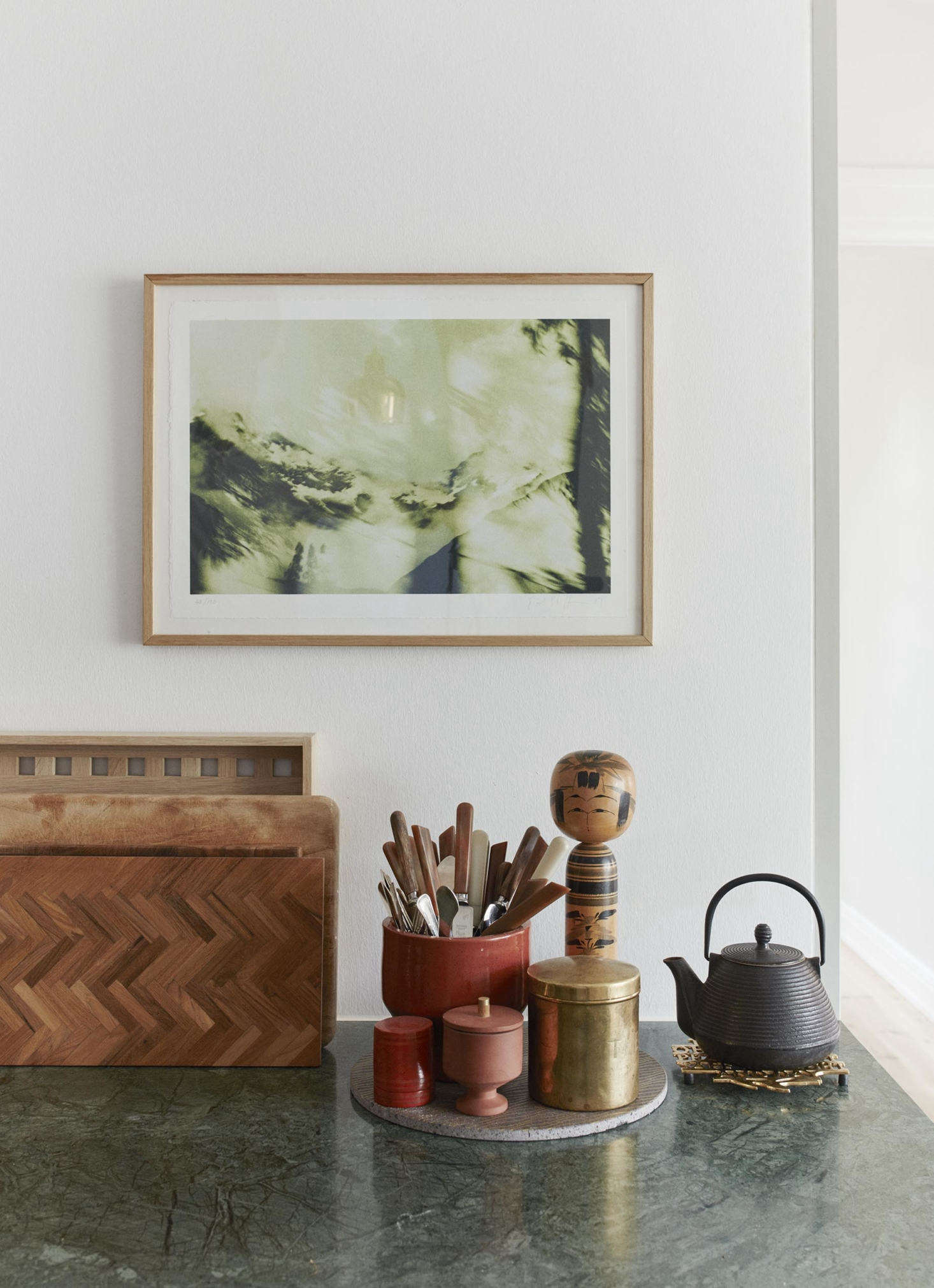 A tray corrals a few kitchen essentials, including a petite terra cotta Edge Sugar Bowl, designed by Copenhagen-based design duo Stilleben, and a vase full of utensils. (For a look at a few of the company&#8