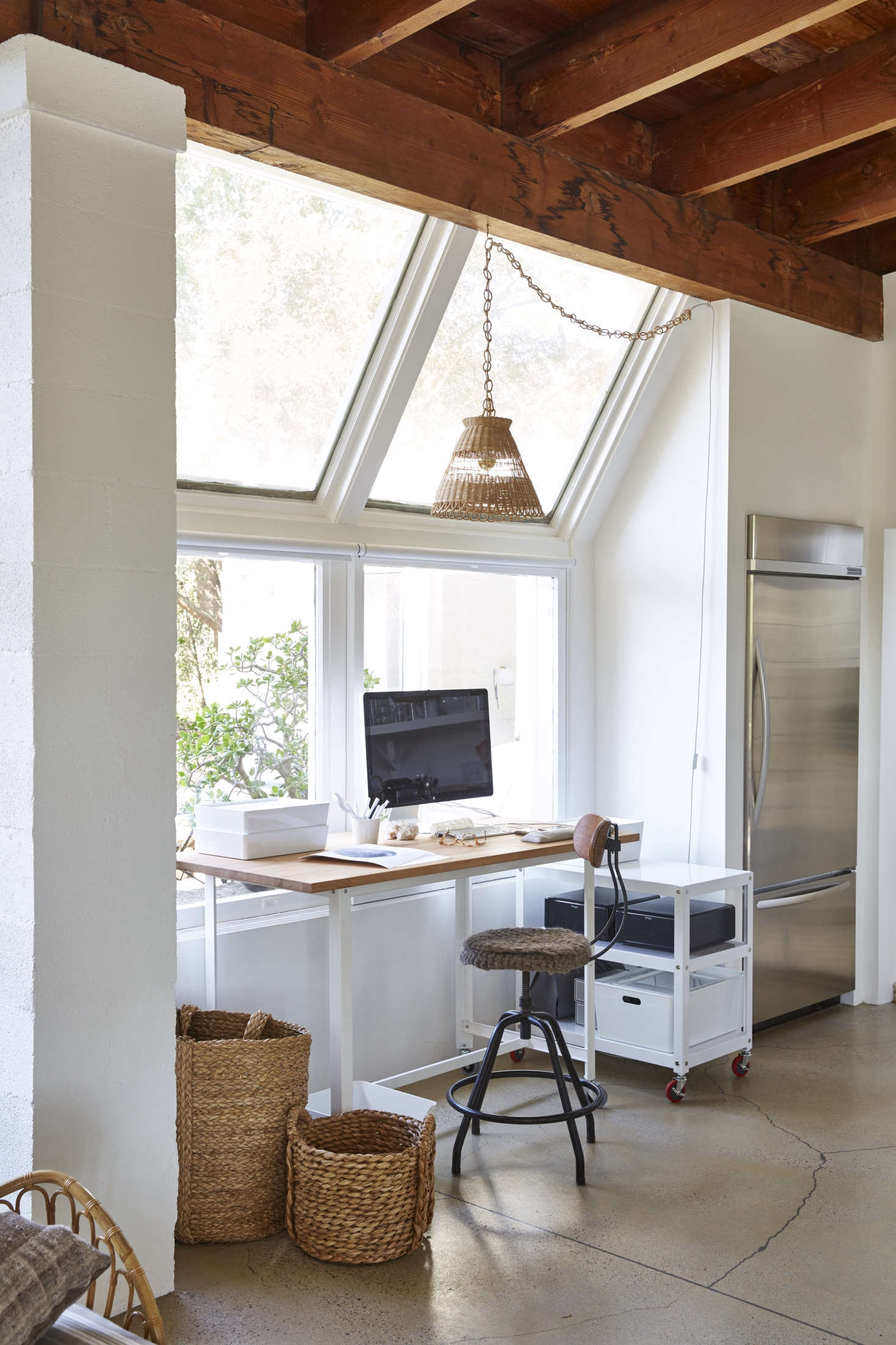 A slim workspace, with a clean-lined desk and stool, fits next to the KitchenAid fridge, along with a low credenza on wheels for easy transportation while shooting.