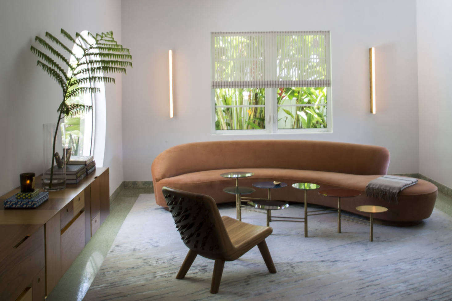 "Seen here in the Miami Beach home of Stephan Weishaupt is the original Vladimir Kagan Serpentine Sofa with Arm from 50 in coral velvet. ""I wanted an organic shape floating in the space,"" says Weishaupt. ""I think it goes nicely with the round window."" The sofa, model 0BSA, is still available to order through a Vladimir Kagan showroom; contact for pricing and more information."