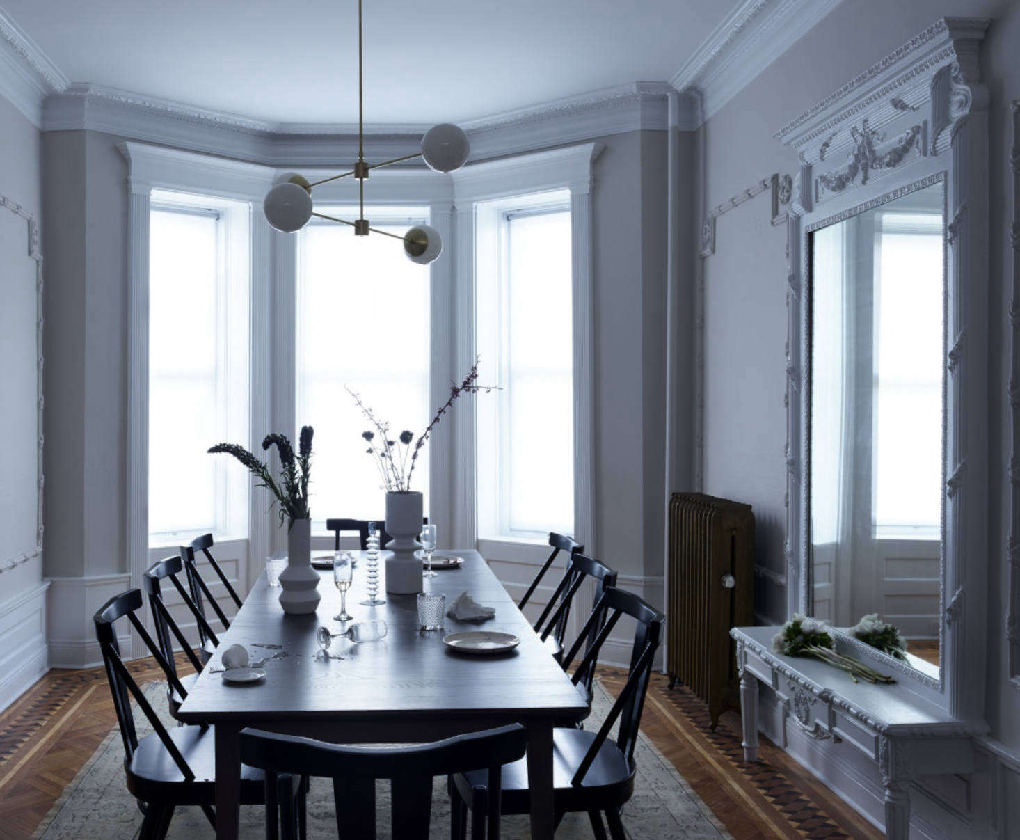 In the dining room, pale paint—Benjamin Moore's Collingwood in a matte finish at 25 percent dilution—lends a slightly ghostly feel. The molding here, including the original built-in mirror, is painted over in Benjamin Moore's Decorator's White in semi-gloss.