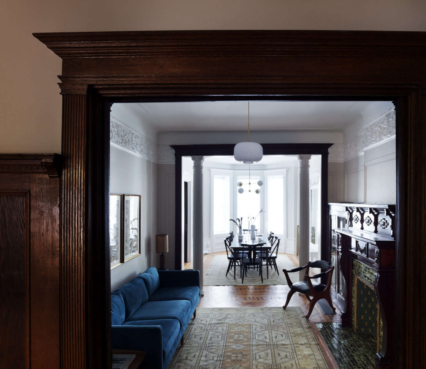 Just off the dining room is a narrow parlor, fitted with a blue velvet couch across from the original fireplace. Otherwise it's left sparse, to allow easy movement between dining room and living room.
