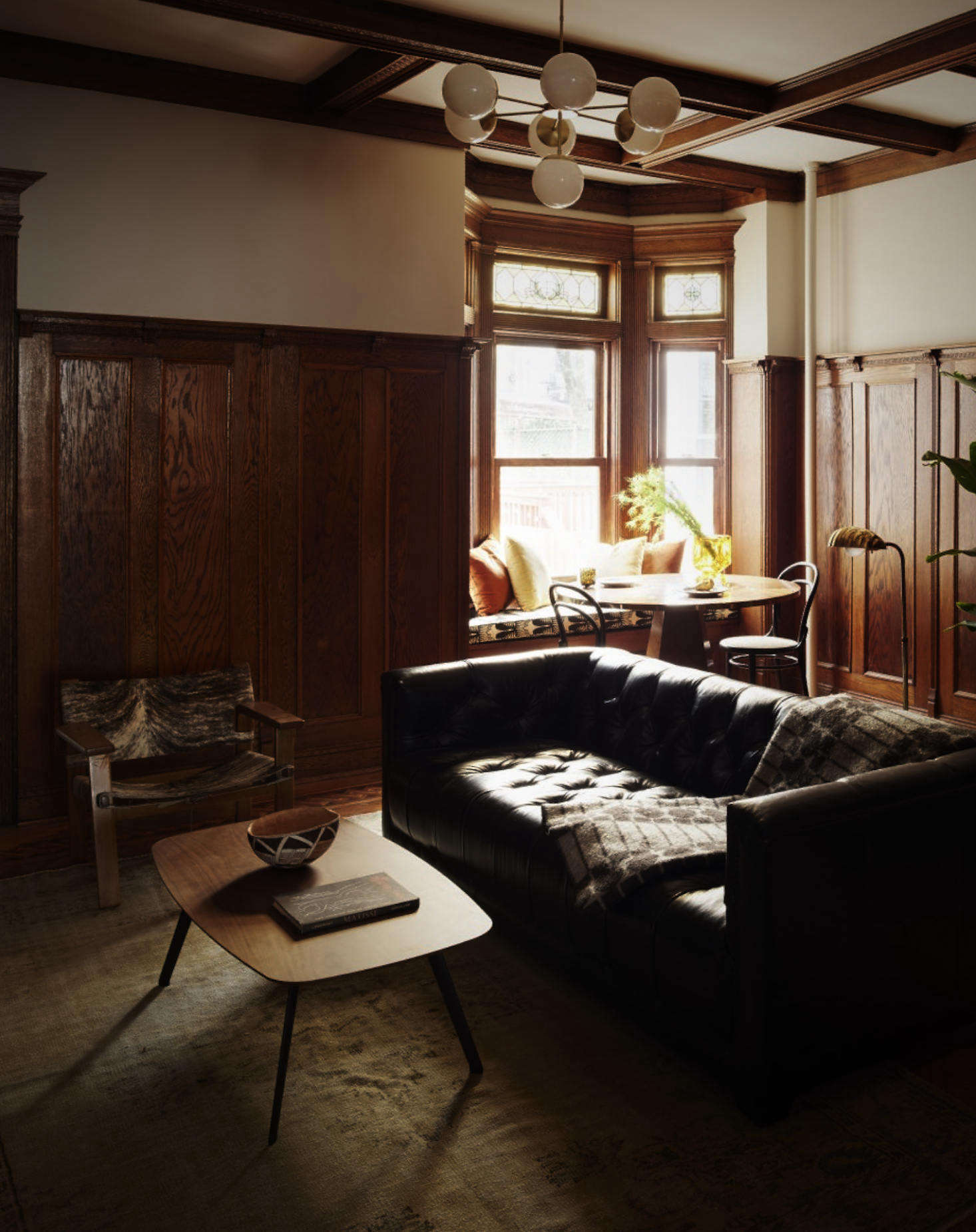In the living room, Spain reserved the house's warm Arts and Crafts-style wood paneling and coffered ceiling.