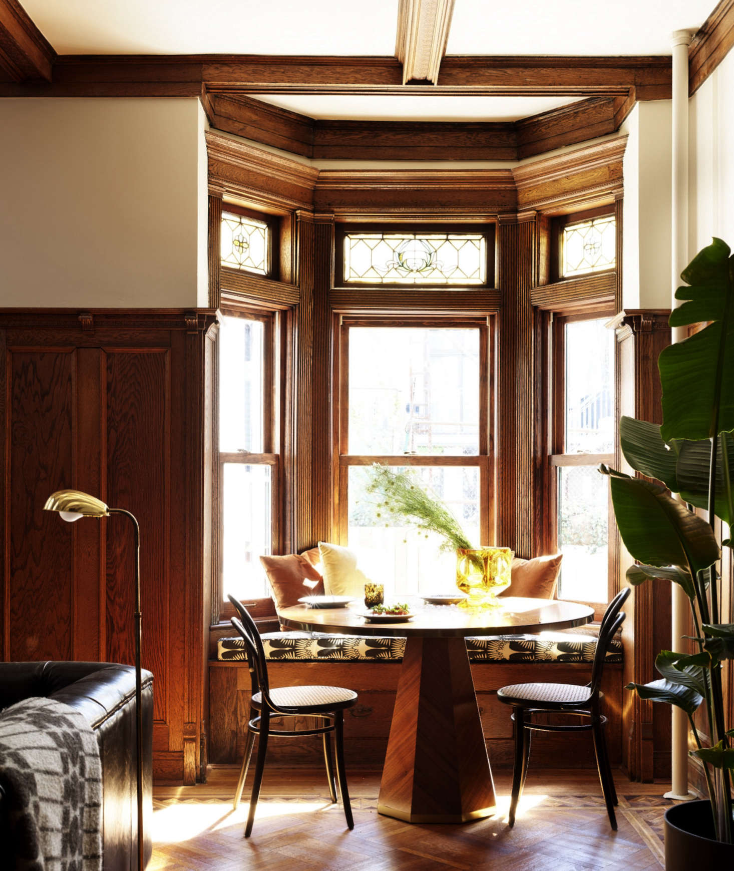 Caned chairs flank a breakfast table, set into a bow window. The stained glass at the tops of the windows is original.