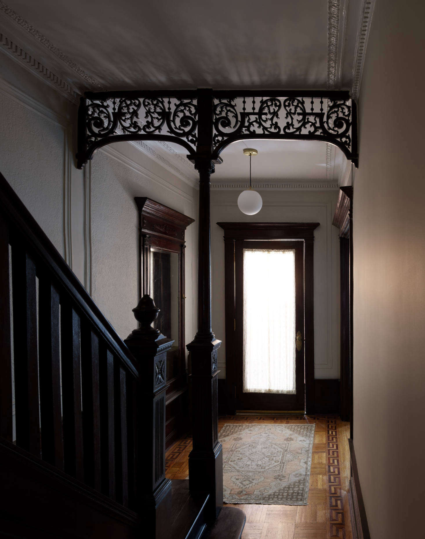 The dramatic first-floor hallway, with elaborate moldings preserved, sets the stage for the rest of the house.