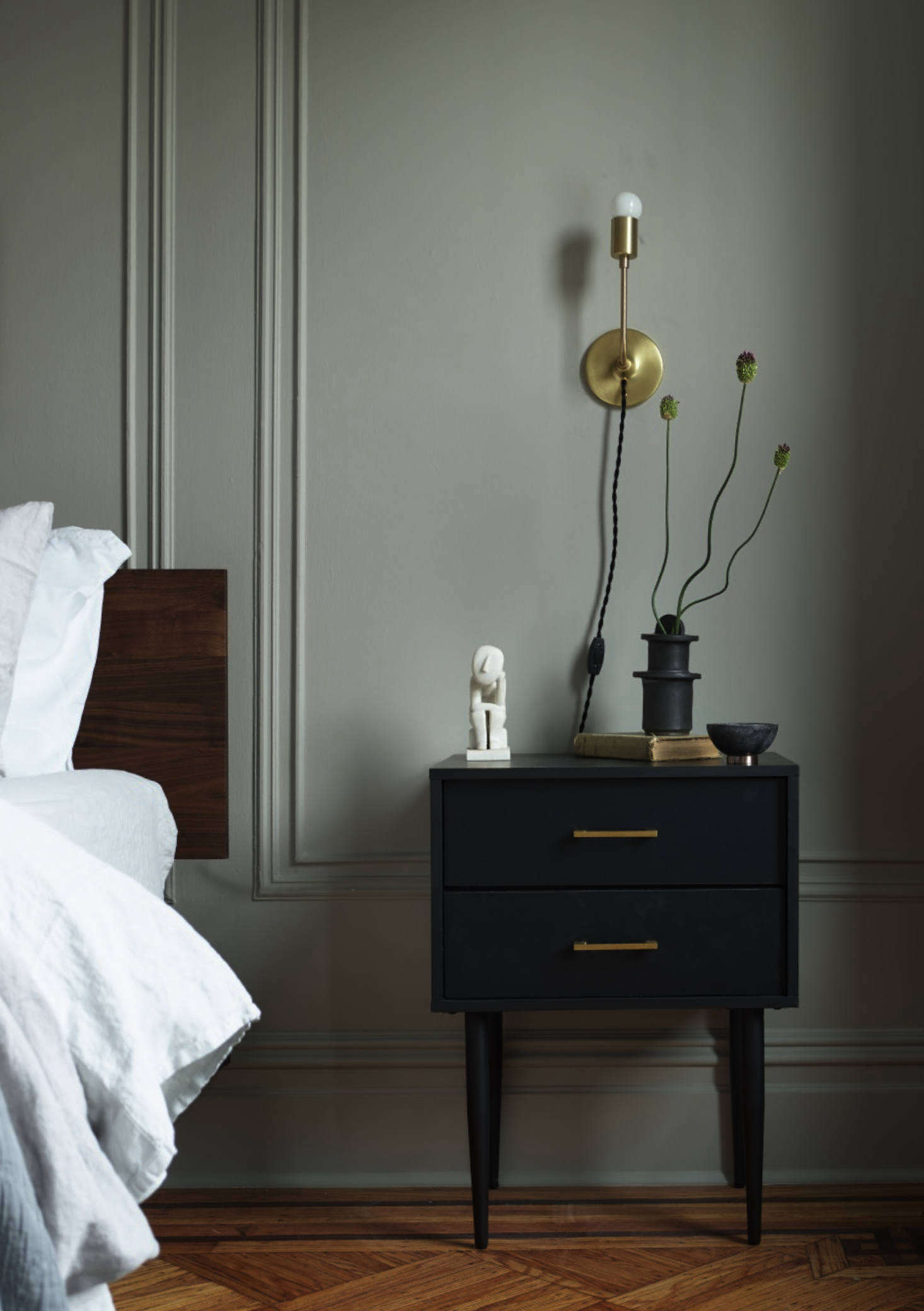 Sculptural flowers on the nightstand. The bedside lights are the Astrid Sconces from Schoolhouse.