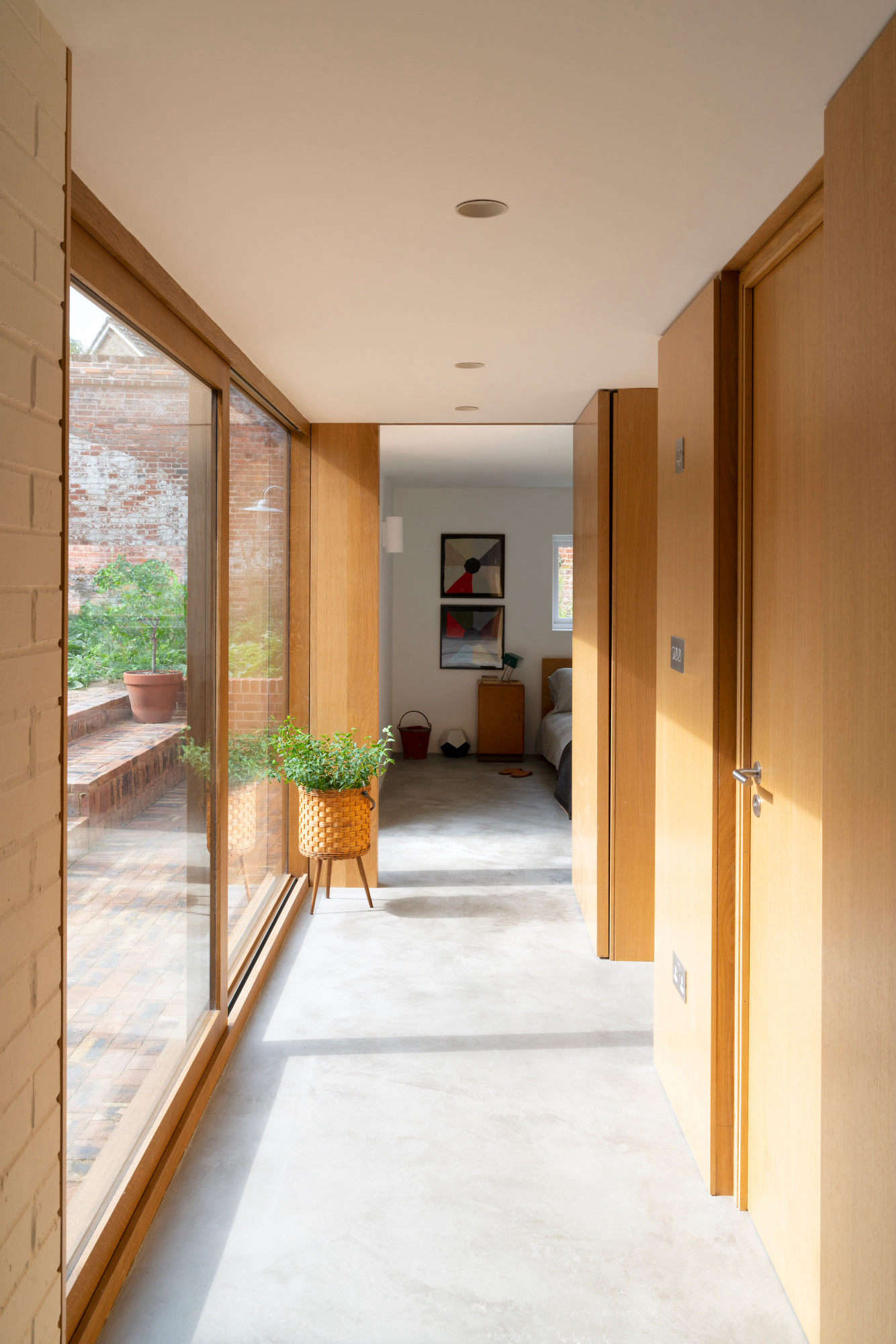 "The addition's glazed hallway overlooks the garden. Deben Joinery did all of the woodwork: shown here, walls and doors in oak. The floor is micro-concrete. ""I wanted the extension to look like a new addition and not a pastiche of the original building,"" says Sandy, ""but they have things in common: simplicity and good light."""