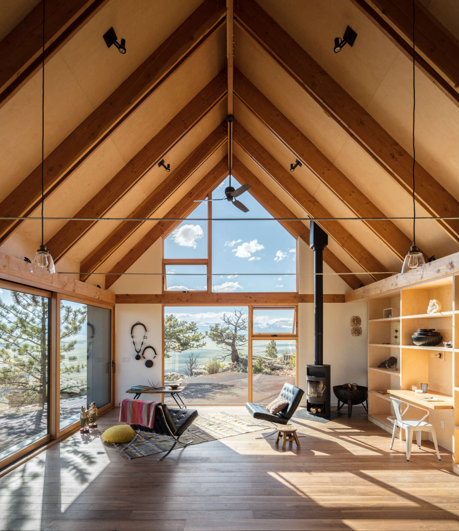 """Del Gaudio lined the 1,300-square-foot interior with clear-sealed Baltic birch plywood and used Douglas fir for the rafters and other exposed framing. The rustic-grade walnut floor has radiant heating set in a concrete slab, and there's also a Rais wood stove powerful enough to heat the entire cabin: """"when the stove is cooking, a thermostat shuts off the radiant heating,"""" says del Gaudio."""