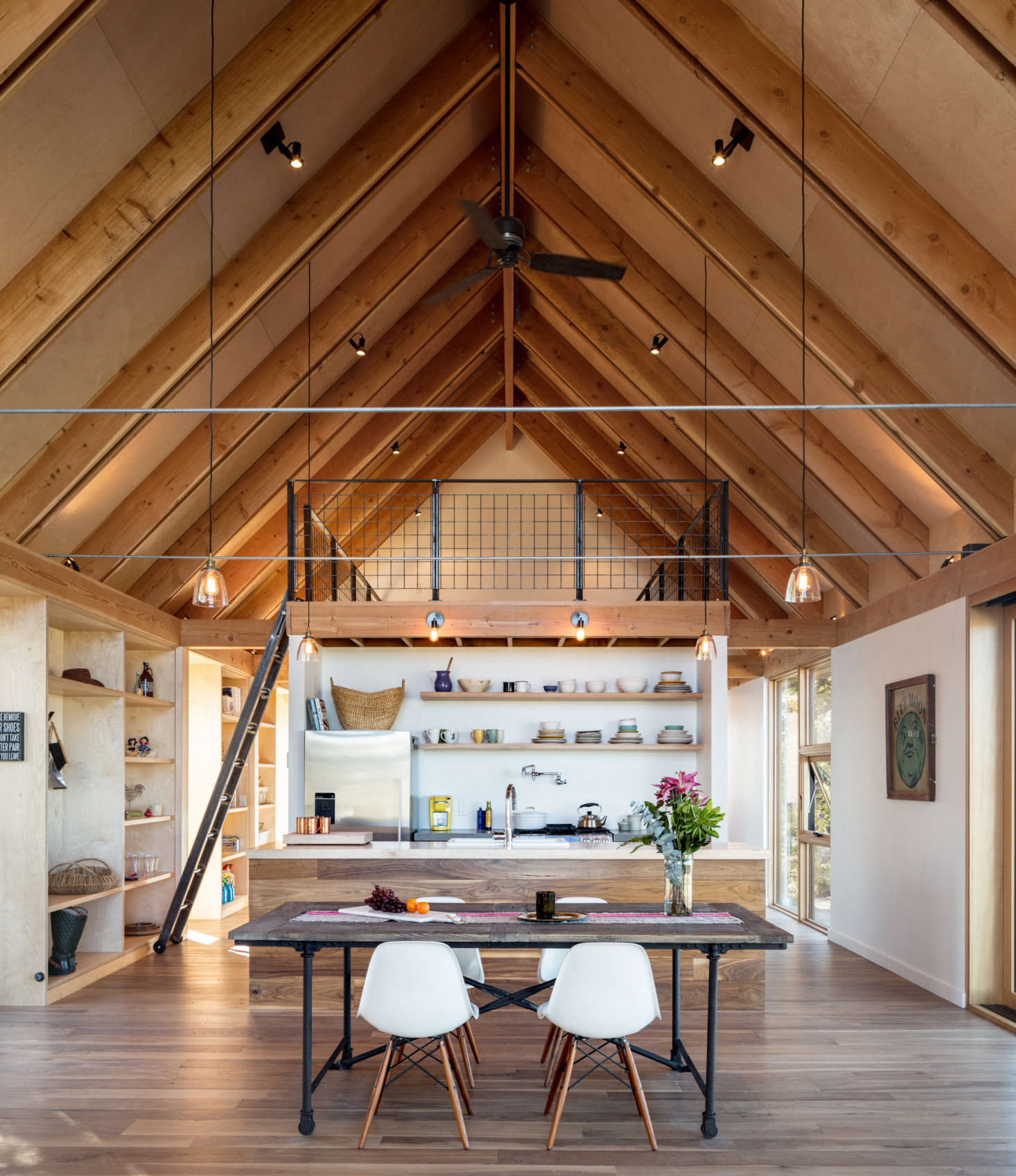 """An island, finished in the same walnut as the floor divides the kitchen from the rest of the room. Blum uses the 180 square foot loft as a painting studio, storage space, and extra guest room. """"It's accessed by a ladder and is flexible space that keeps the main level clutter free,"""" says del Gaudio."""