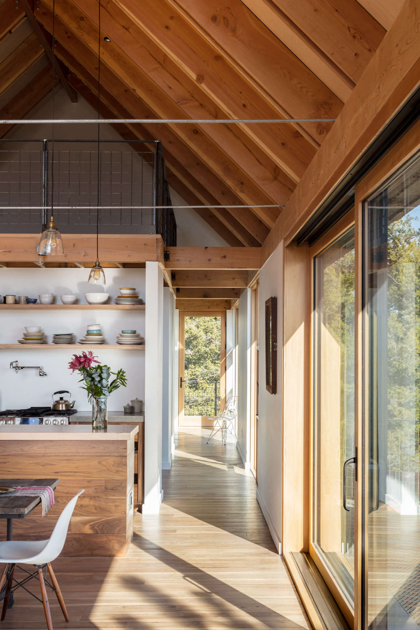 """The kitchen island has a John Boos butcher block counter and the sink counter is cast-in-place concrete. The loft's steel railing is enclosed with welded wire mesh: """"it's an inexpensive agricultural staple sold in sheets,"""" says del Gaudio. """"The version we used has four-inch squares—they can't be any bigger to pass code."""""""