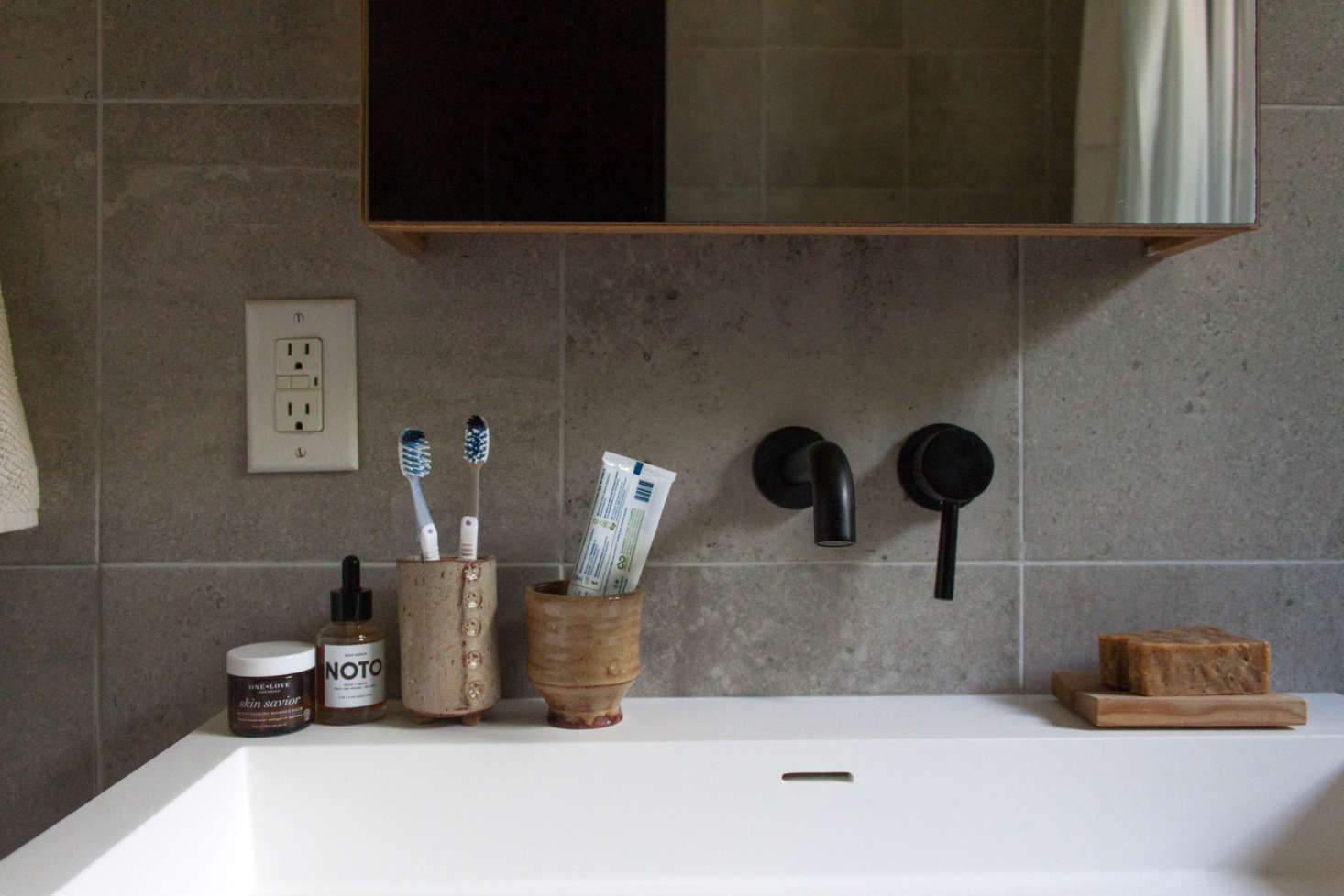 """""""The tile was sourced from a local shop, and it's now discontinued. We learned that the hard way when a few of the tiles had to be replaced. Luckily my father-in-law found some,"""" says Gabi. The medicine cabinet is from Wet Style. The ceramic vessels are by Wade Franklin."""