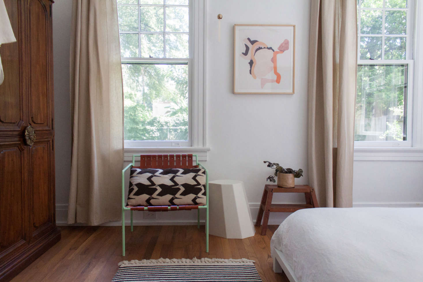 Floor-length Ikea curtains soften the look in the bedroom. The Amigo Modern chair was a gift from a friend, the wood stool a gift from Gabi&#8