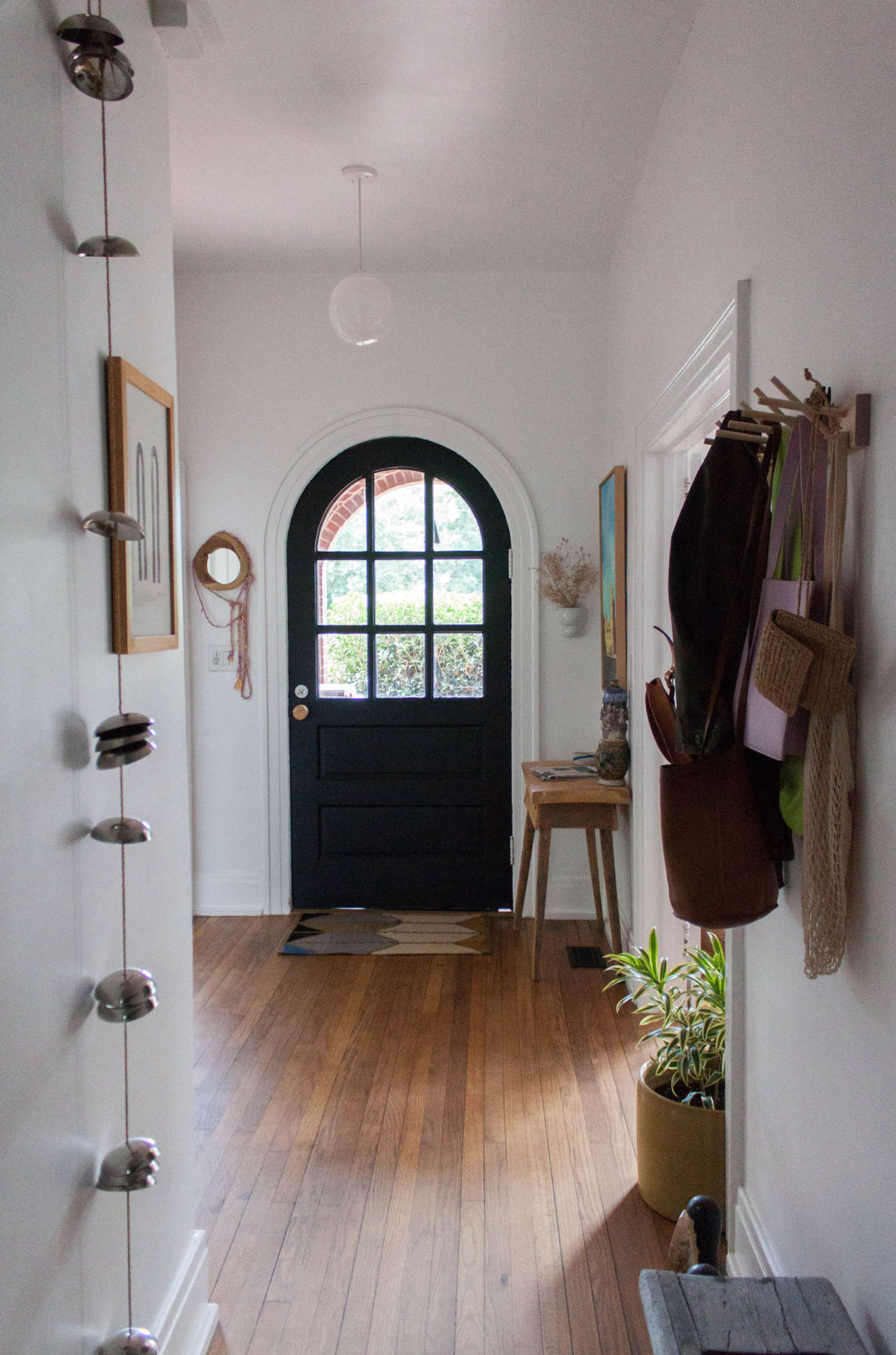 Gabi's eclectic sensibility is apparent as soon as you enter the front door. The pendant light is from Schoolhouse; the doormat is by Alyson Fox for Hawkins NY; the console is from an antique store; and the Iris Hantverk hooks are from EA/ST Co.