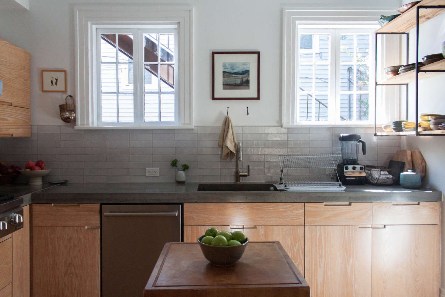 """""""Other than the bathroom, the kitchen was the only room that was fully gutted. My father-in-law helped us figure out the best use of space, and even then we added the butcher block island because we could use the extra counter space,"""" Gabi tells us. """"The cabinets are custom, as are the concrete countertops. I try to balance out all of the warm wood tones with art and pottery."""""""