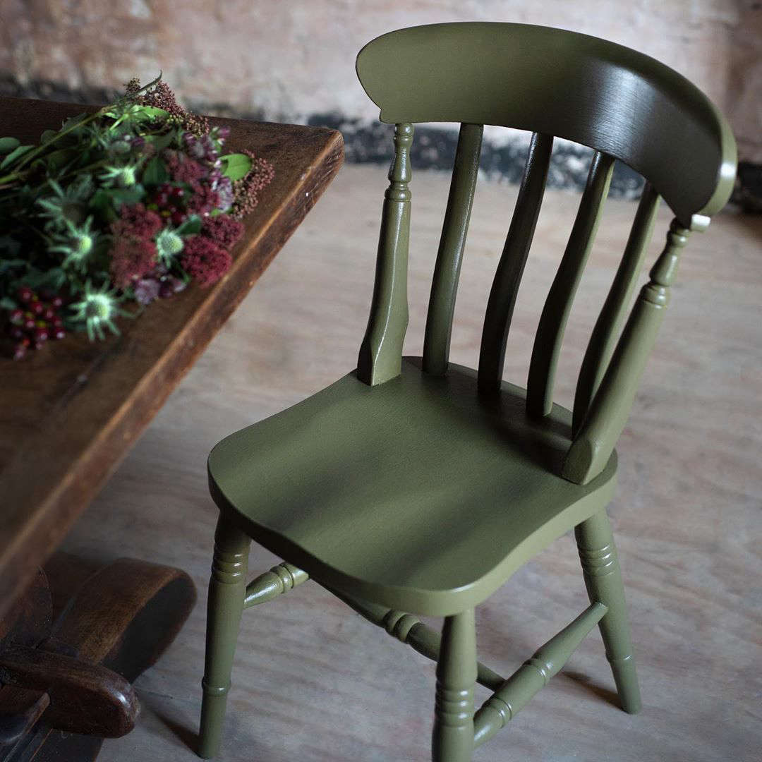 """A dining chair painted in Dried Kelp, which """"brings in elements of nature's deep seas and creates a moody dining room ambience."""""""