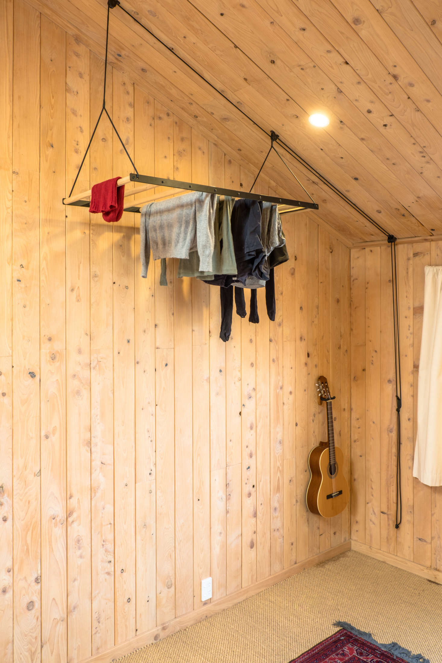 A George & Willy pulley system drying rackhangs in a corner of the master bedroom where it takes up little space and allows clothes to dry in the warmest air. Read about the design in Object of Desire: A Hanging Laundry Rack.