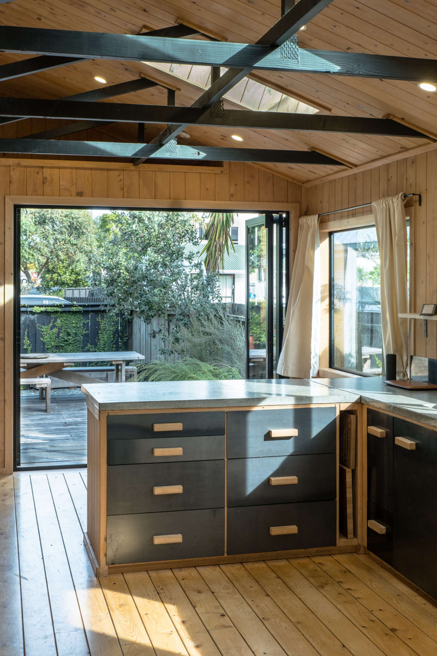 """The kitchen island is framed with the same wood used throughout and the drawers are plywood with steel fronts. George and Will poured the concrete counter themselves in their workshop: """"it's the first one we ever made and is actually rather rough, but it gives the room lots of character."""""""