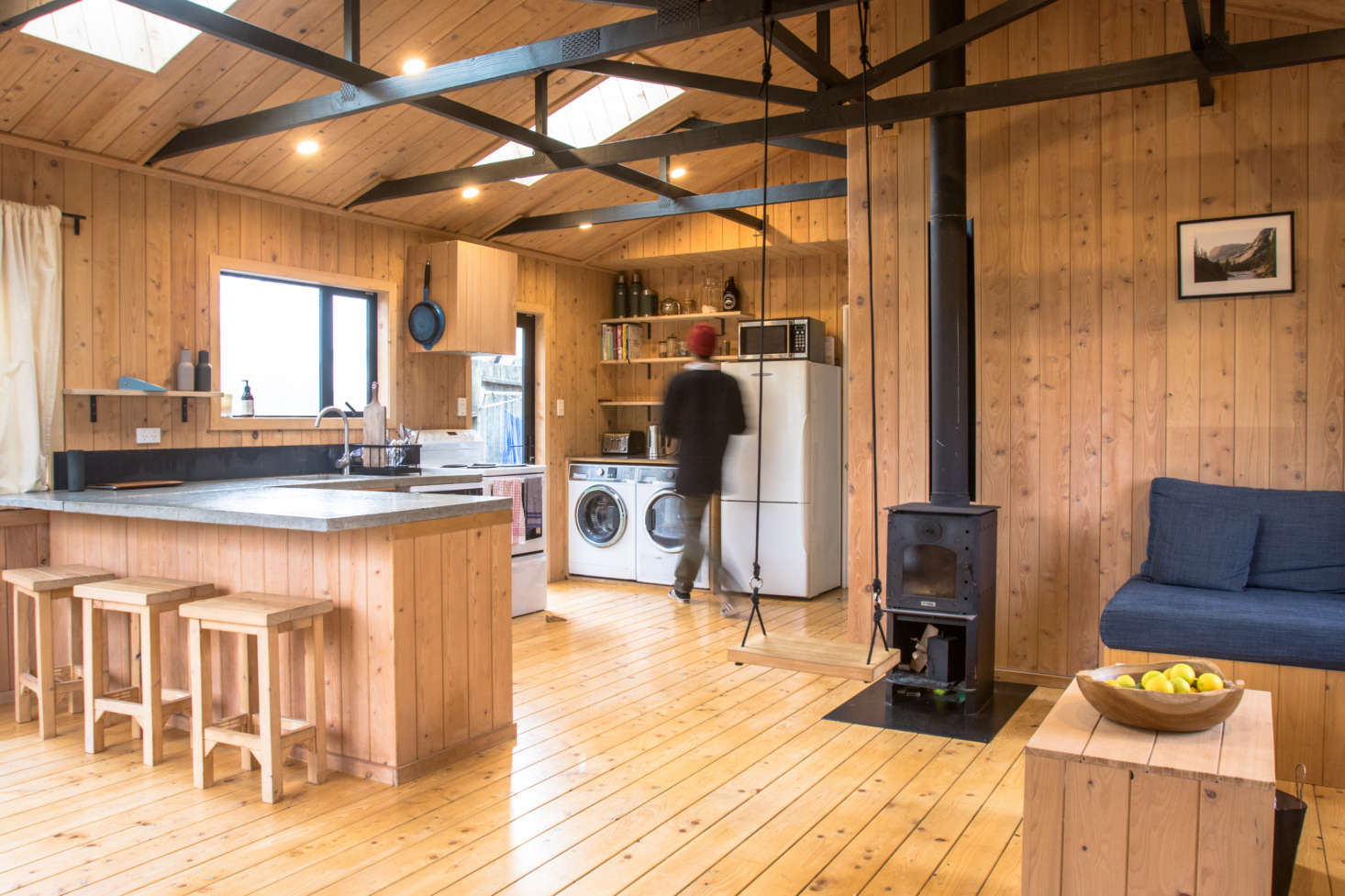 """George describes the look of the interior as """"a mixture of a forestry cabin and ski lodge"""" and says """"macrocarpa has such a nice smell—it's very welcoming and everyone who comes in for the first time comments on it."""" Work was done on the 100-square-meter (1,076 square-foot) interior in a busy six-week stretch, and then George and Hannah moved in; over the course of the following two years, the exterior was finished during weekends and vacations."""