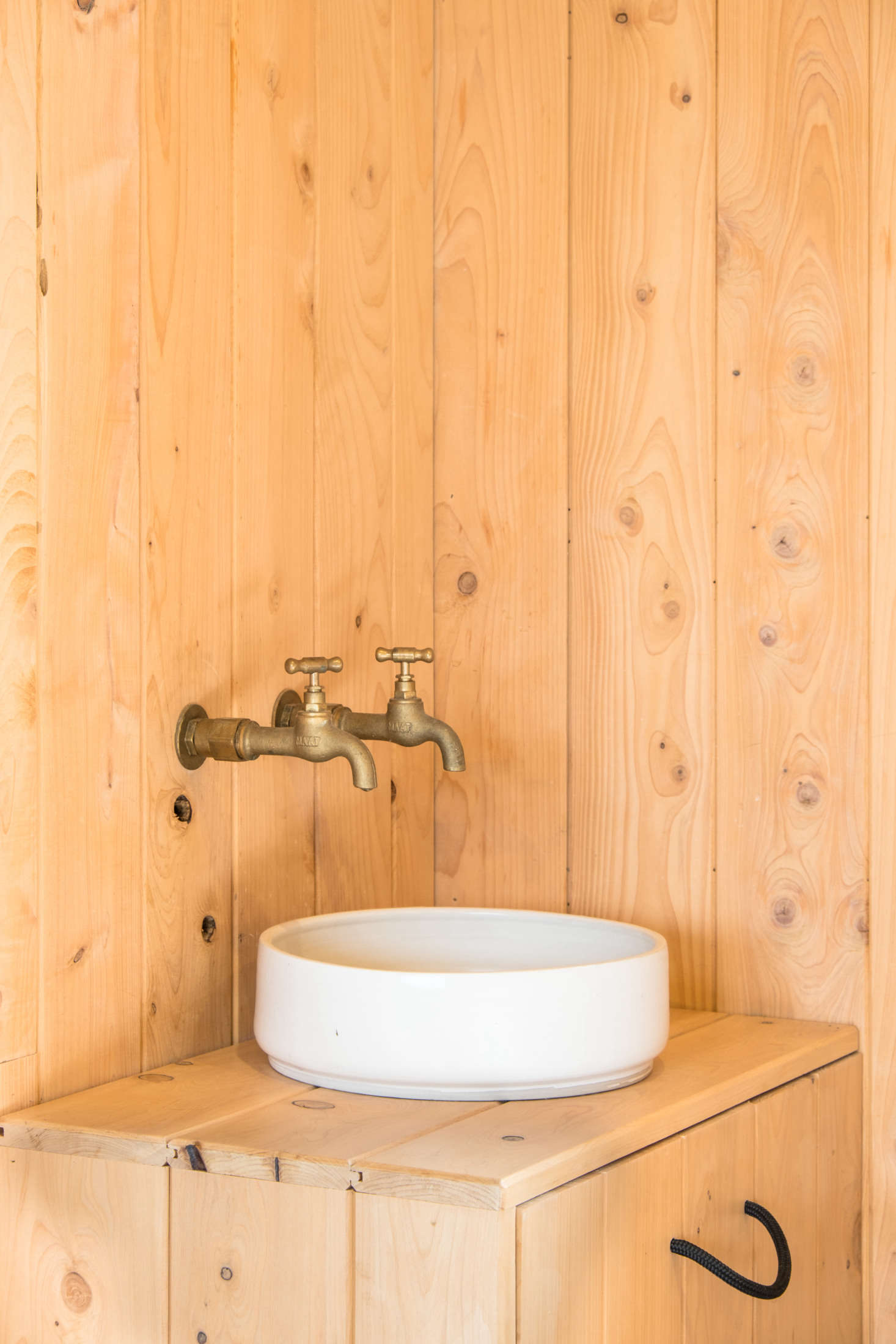 """""""When we were lining what had been thegarage, there were two taps from an old laundry sink, so we decided why not have a sink in the bedroom for brushing teeth and getting water,"""" says George. """"Will had just made the basin at a pottery course and it was perfect for here; we added the surround for storage."""""""
