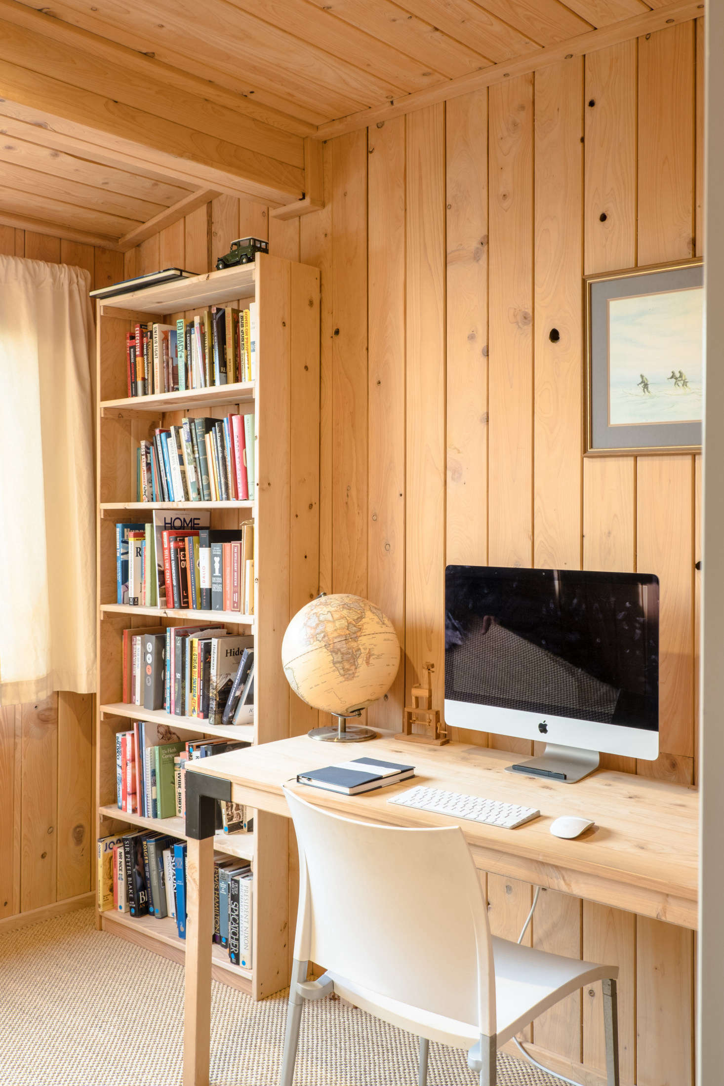 The fully paneled office has a desk and bookshelf that George fabricated from leftover macrocarpa exterior cladding. He says he's slowly building a book collection that he hopes will one day line the room.