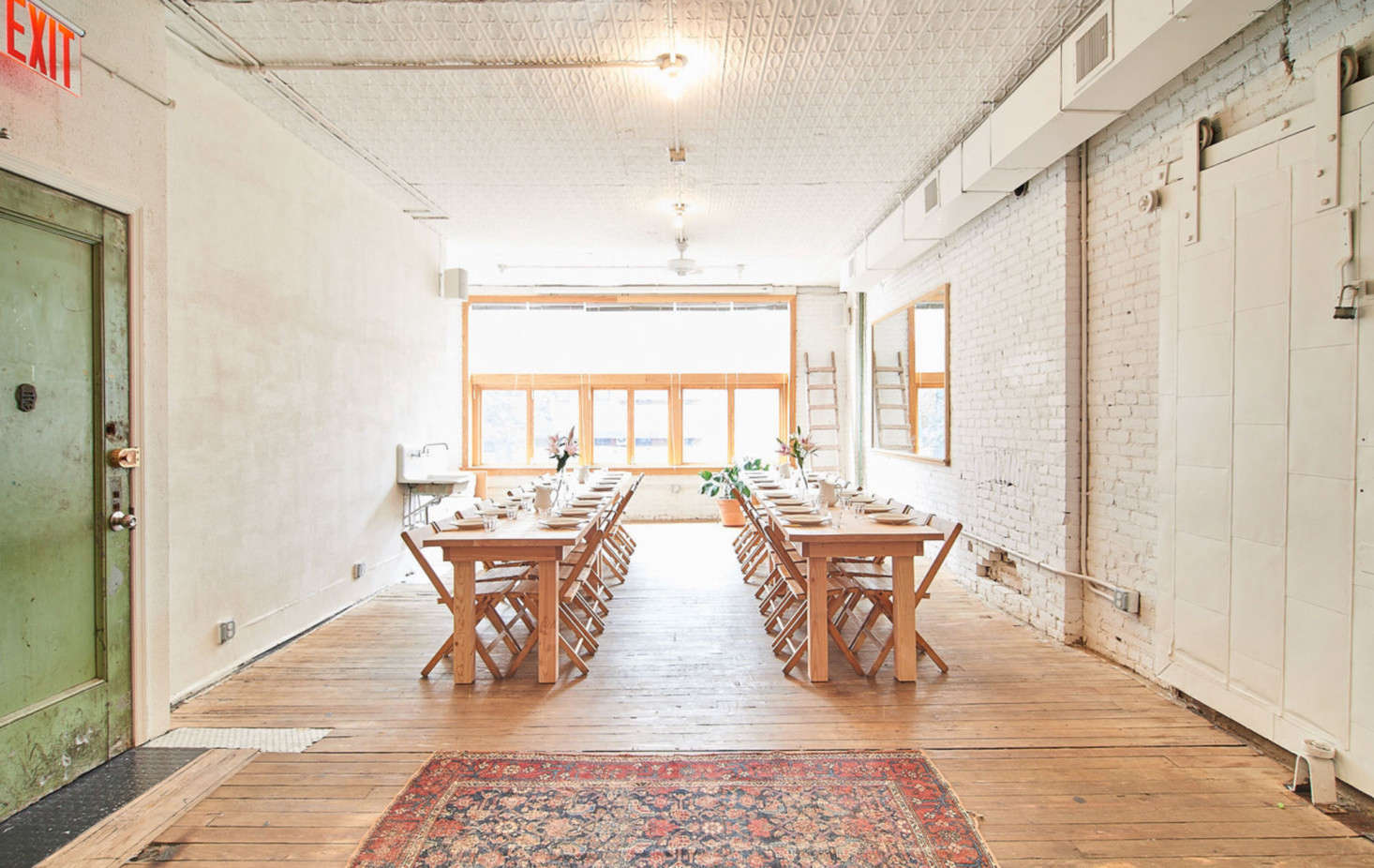 """The dining space. The green door is original to the building and was left untouched. The wood floors are also original. """"Where the original wood had rotted, I filled it in with tile instead of wood, in whatever shaped was needed,"""" says Poe."""