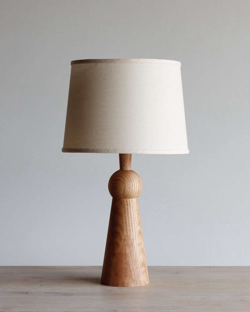 Wood accents warm up the black, white, and gray palette. Lostine's Bella Skirt Lamp, featuring an oak base, is $655.
