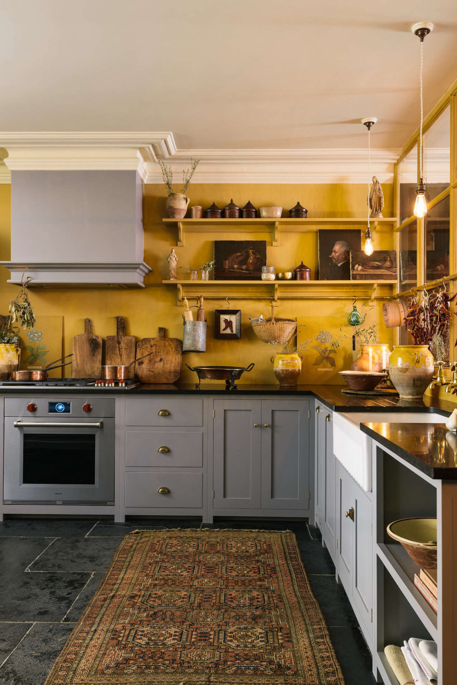 Parker sourced many of the decorative touches—confit jars, oil paintings, Spanish baskets—from flea markets and antique fairs. The integrated stove is by Wolf. The countertops are Belgian Blue Limestone.