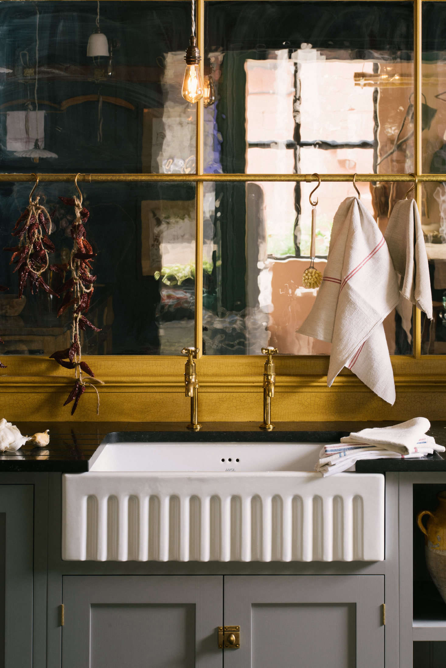 The Single Fluted Sink is from deVOL, as is all the hardware, including the Aged Brass Mayan Taps by Perrin & Rowe and the Hanging Rail. A partition featuring heritage glass separates the Real Shaker Kitchen from another kitchen just beyond it.